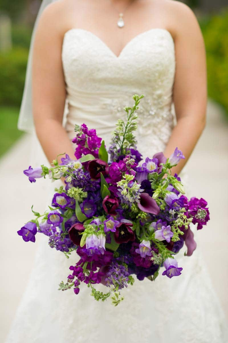 Bride Holding Green And Dark Purple Bridal Bouquet