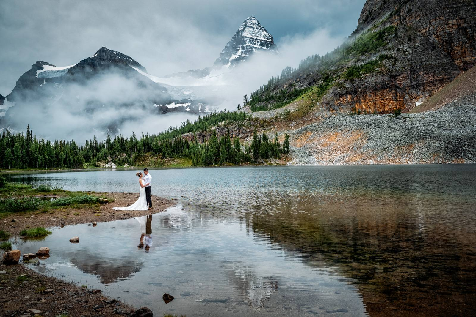 Bride and groom and reflection of Mount Assiniboine in the lake.