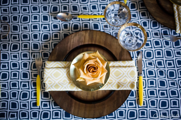 Midnight blue geometric linen paired with yellow silverware and gold accents