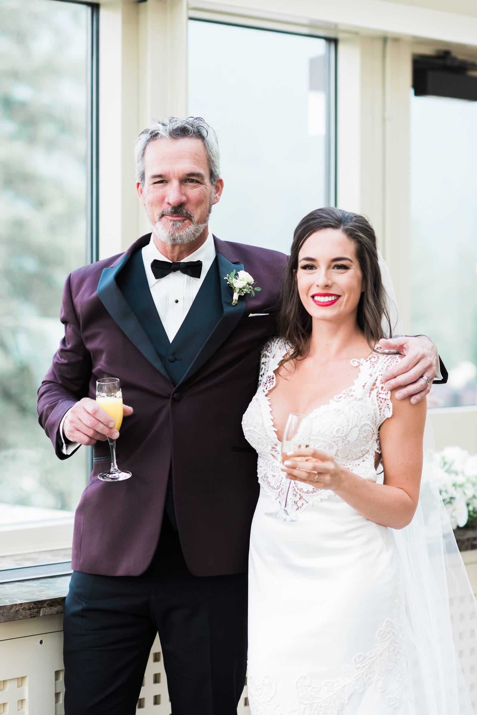 The father of the bride and his daughter pose for a toast and a photo during the wedding reception a