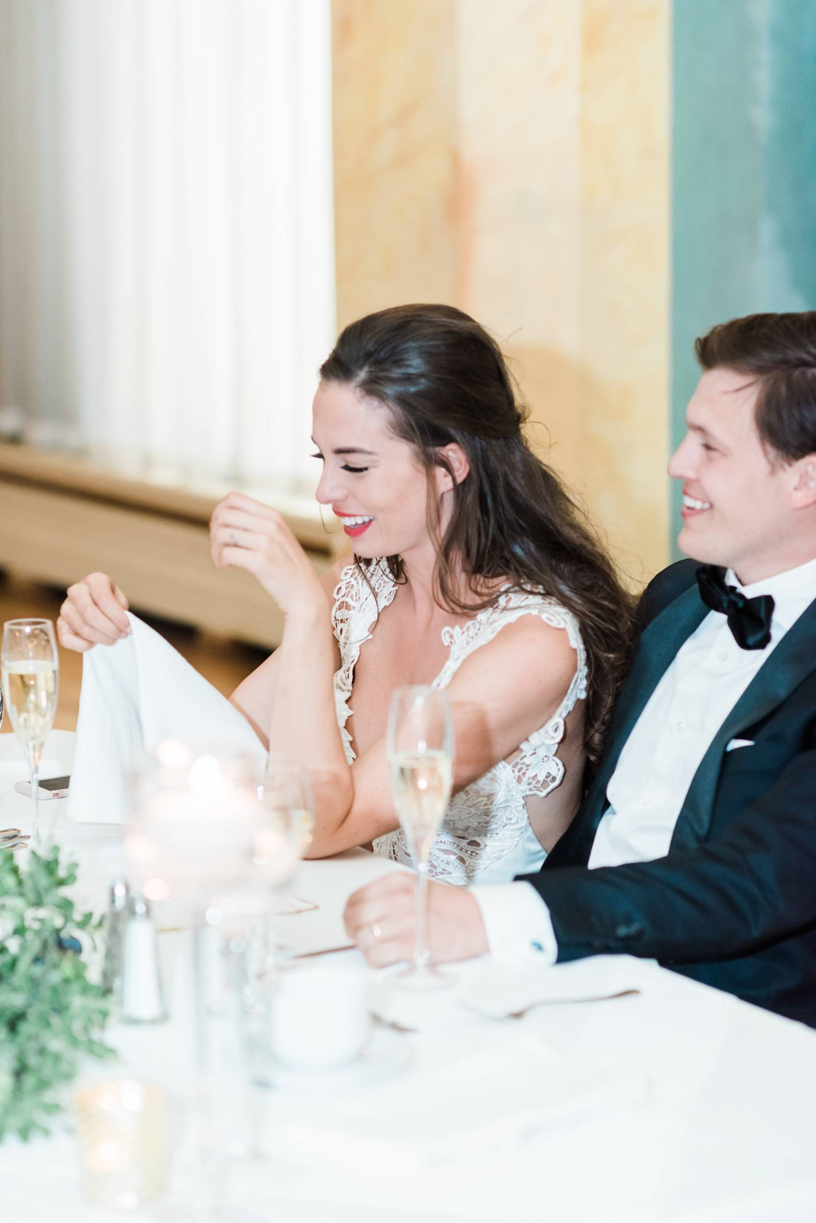 A Bride and groom laughing at their guests toasts at their reception held at the Fairmont Banff Spri