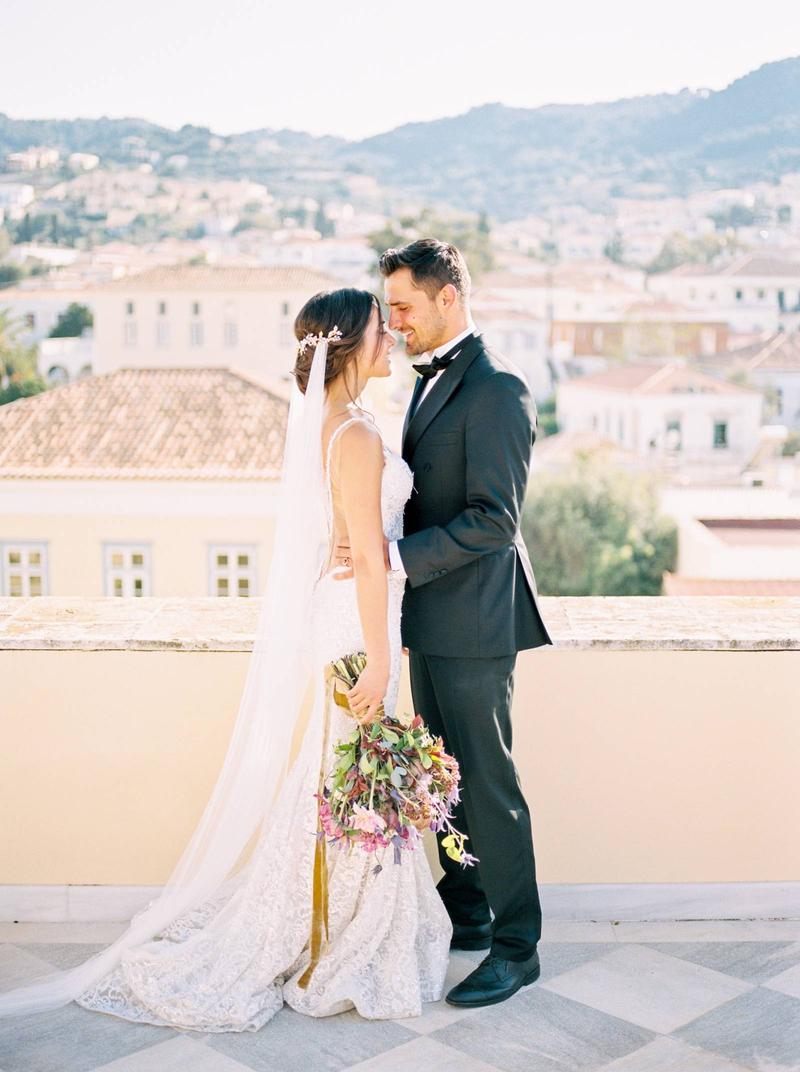 a bride and groom standing on the roof of the Poseidonion Hotel in Spetses Greece on their wedding d