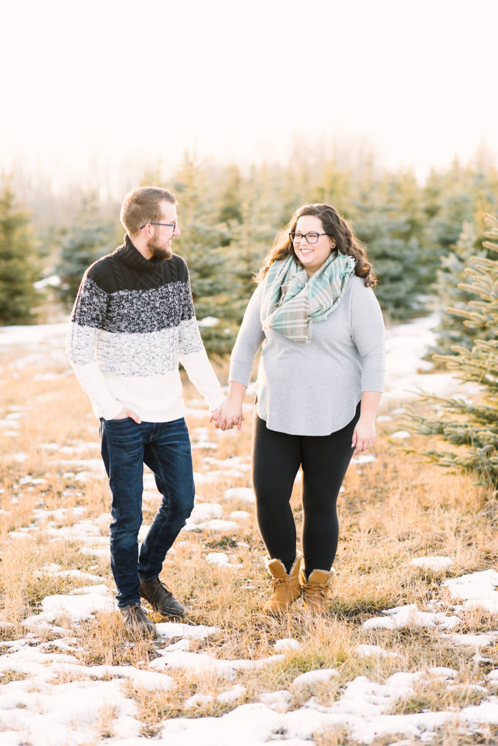 Newly engaged couple walking hand in hand through a Christmas tree farm at sunset
