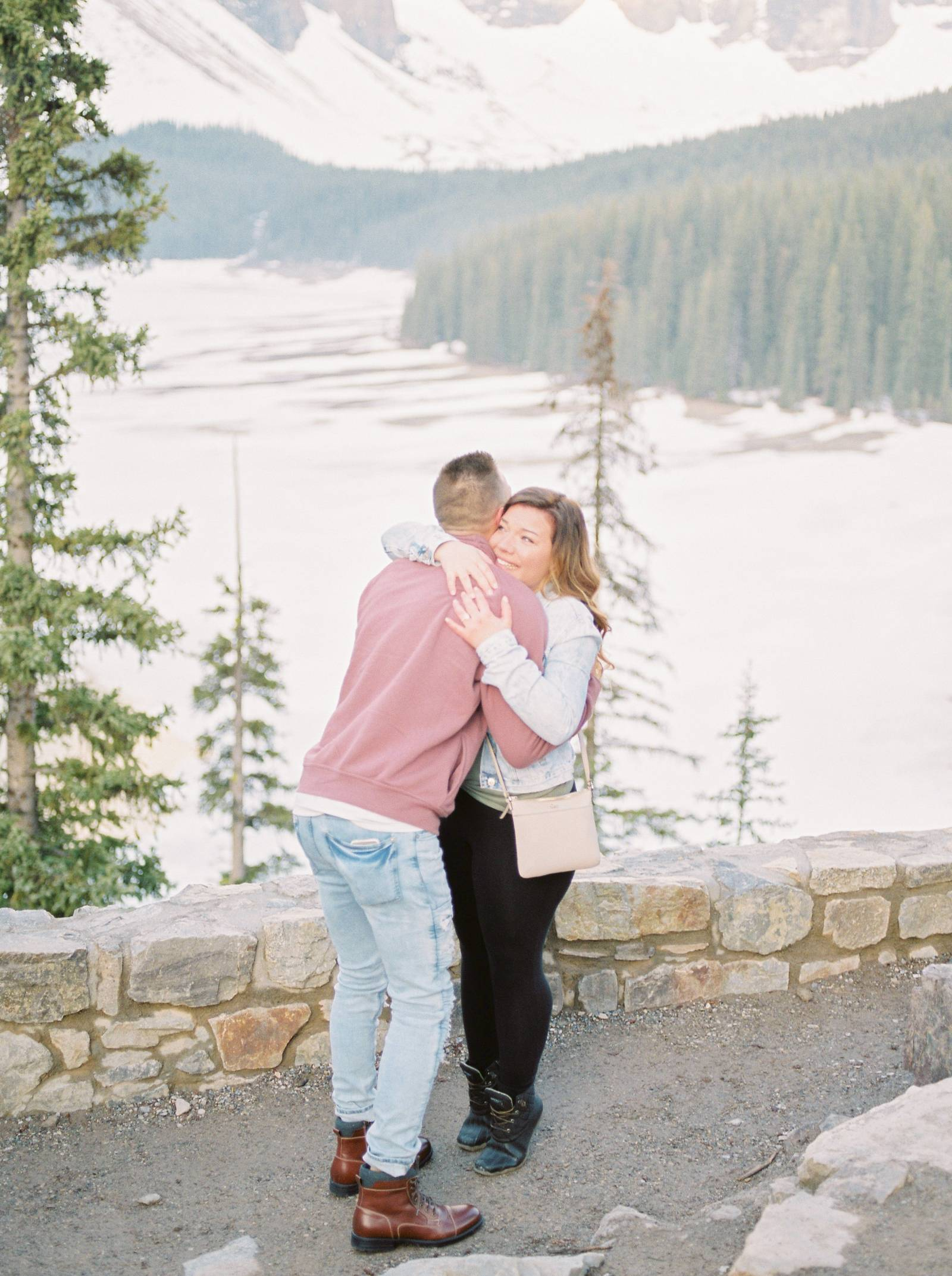 a young couple share an embrace after getting engaged at Moraine Lake in Banff Alberta