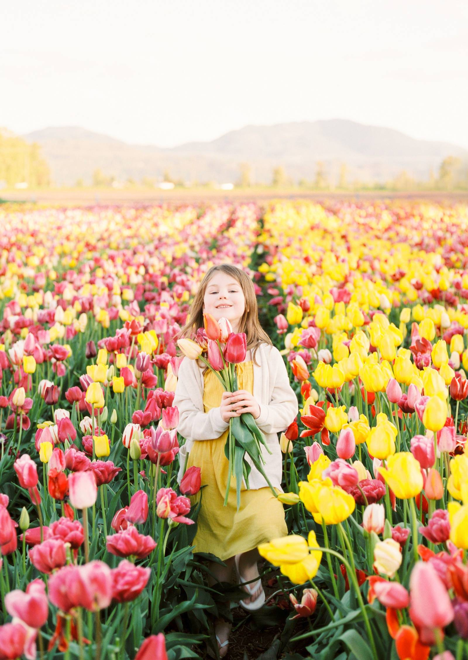 a young girl carries a bouquet of tulips at Abbotsford Bloom festival