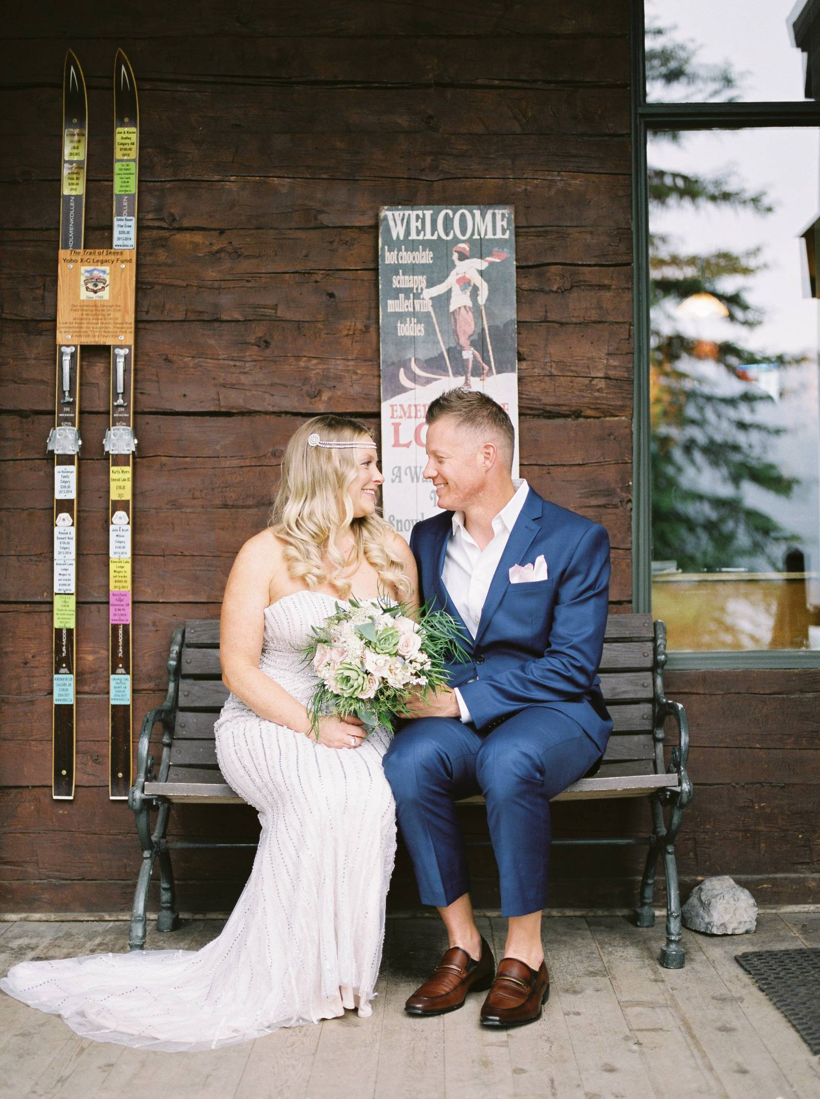 a bride and groom sitting on a wood bench outside the iconic Emerald Lake Lodge