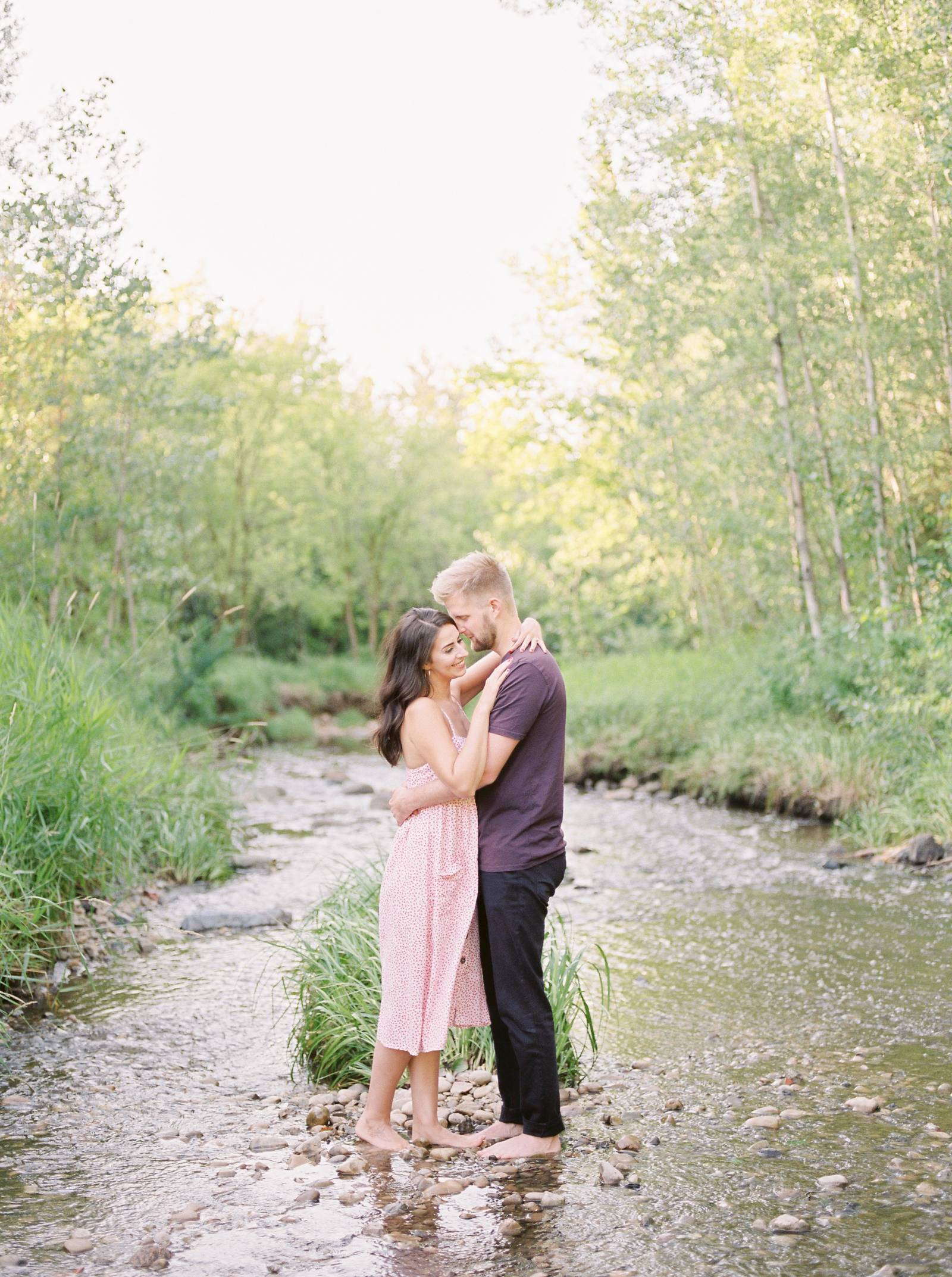 a young man tenderly embraces his fiance on a rocky bank of a spring stream