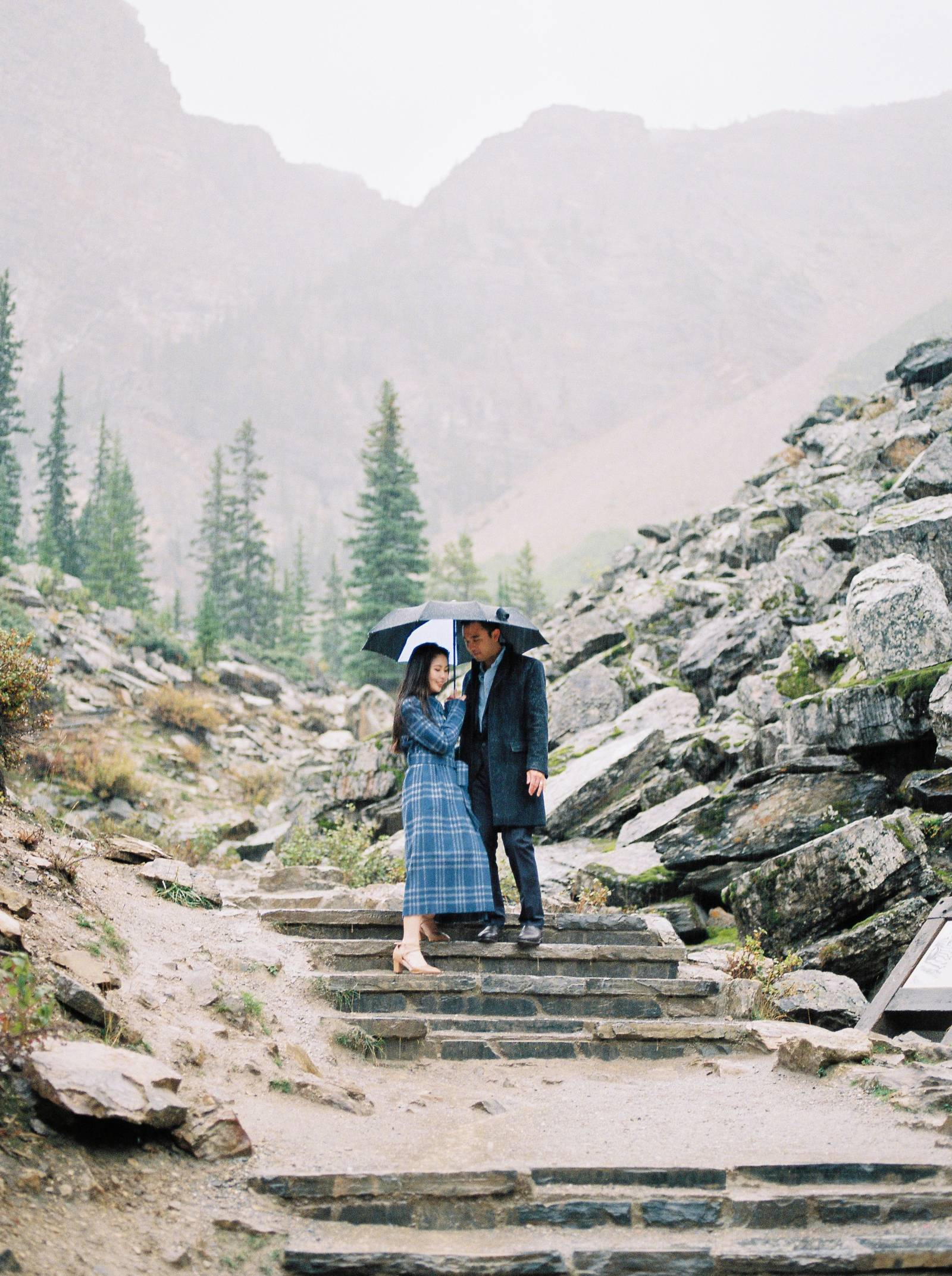 a stylish couple carefully descend the stairs in the rain at Lake Moraine in the rain
