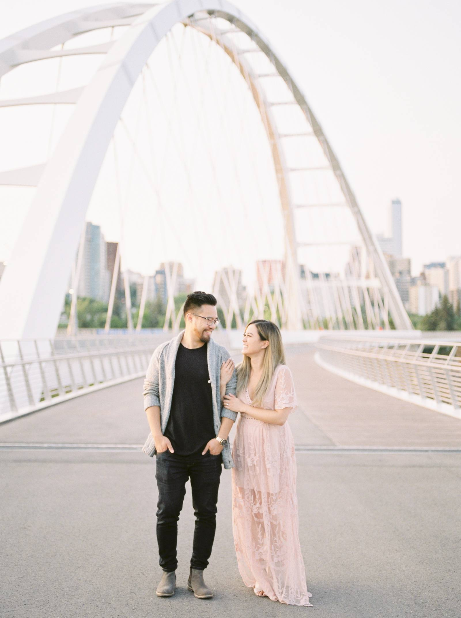 a young engaged couple standing arm and arm on the new Walterdale bride in Edmonton Alberta