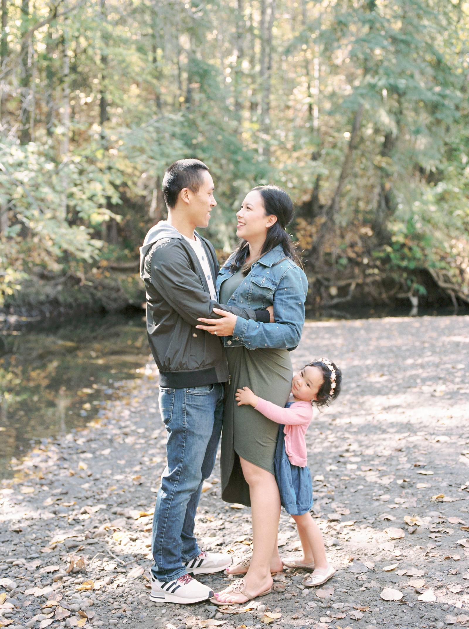 A young Asian family hug on the bank of a fall creek bed in Edmonton