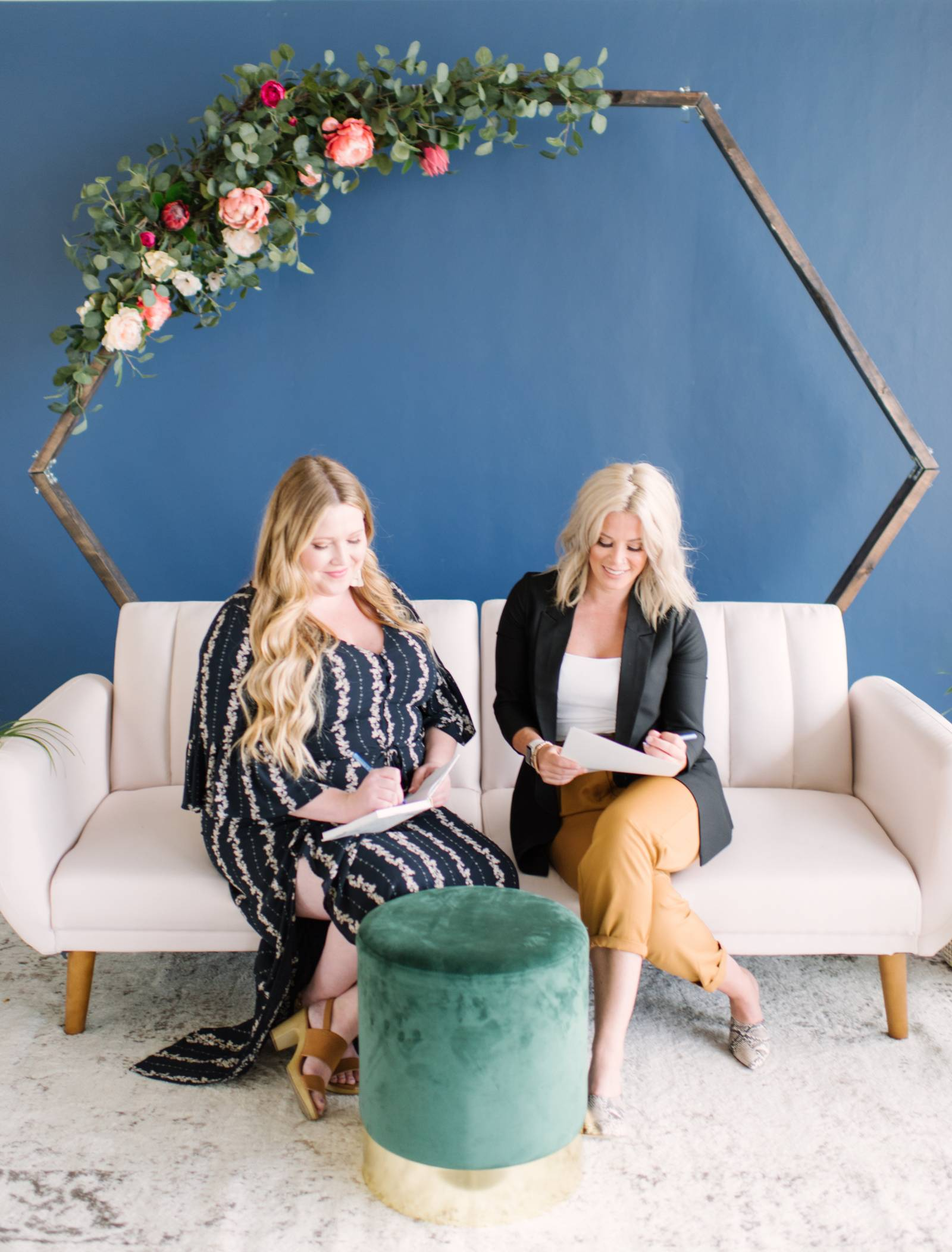 Two Edmonton wedding stylists sitting on a pink couch taking notes