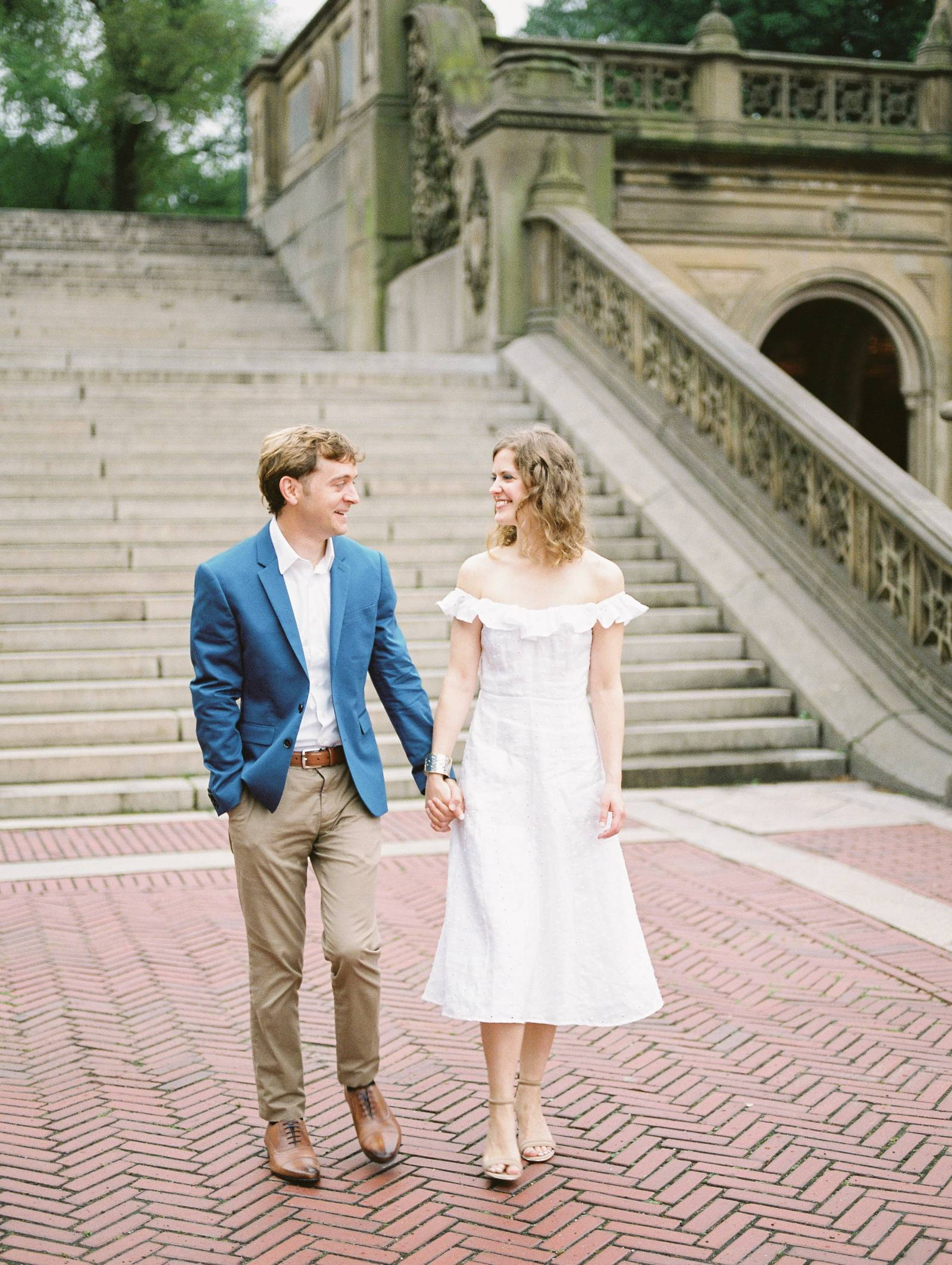 see a young classy engaged couple walking hand and hand through New York Central Park