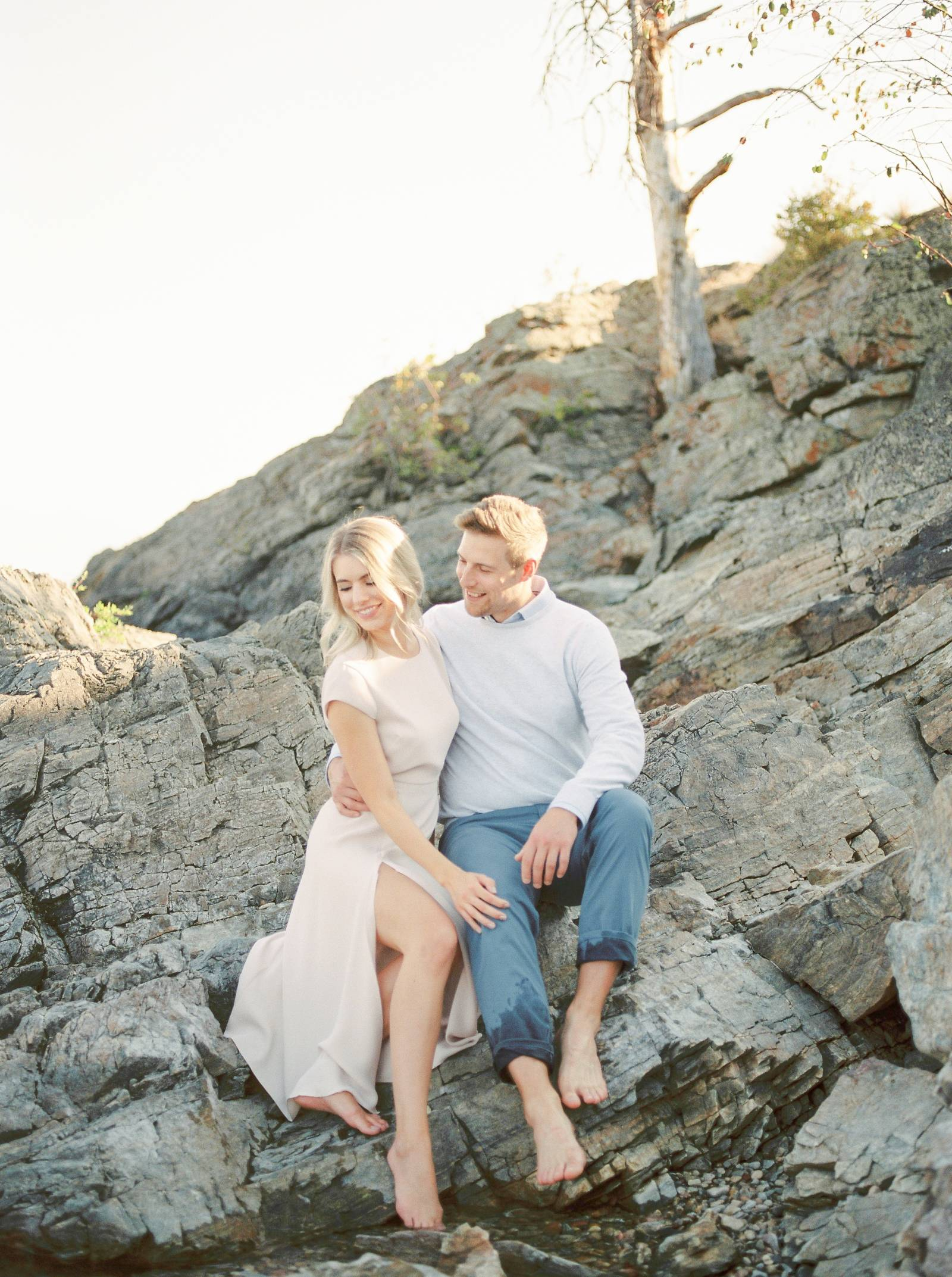 a elegant engaged couple sitting on the rocky beach of scenic Kelowna British Columbia