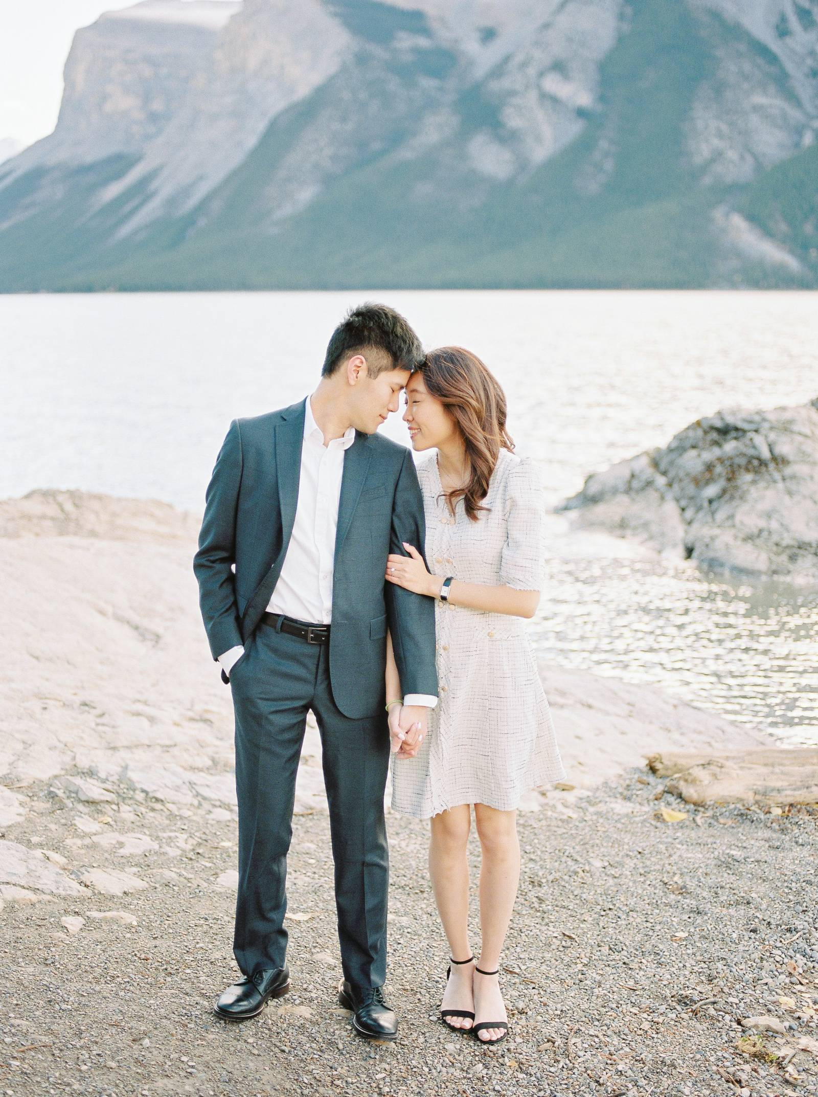 a classy engaged couple embrace while the sun rises over Banff Lake Minnewanka