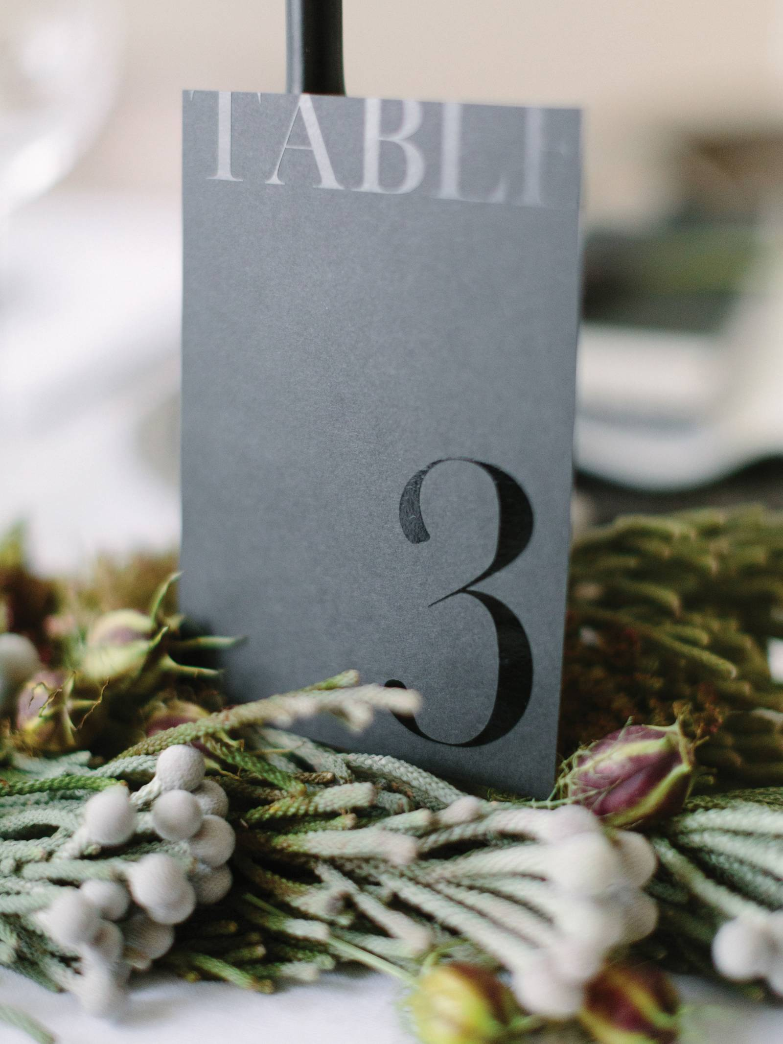 Table number with black ink on gray card stock.