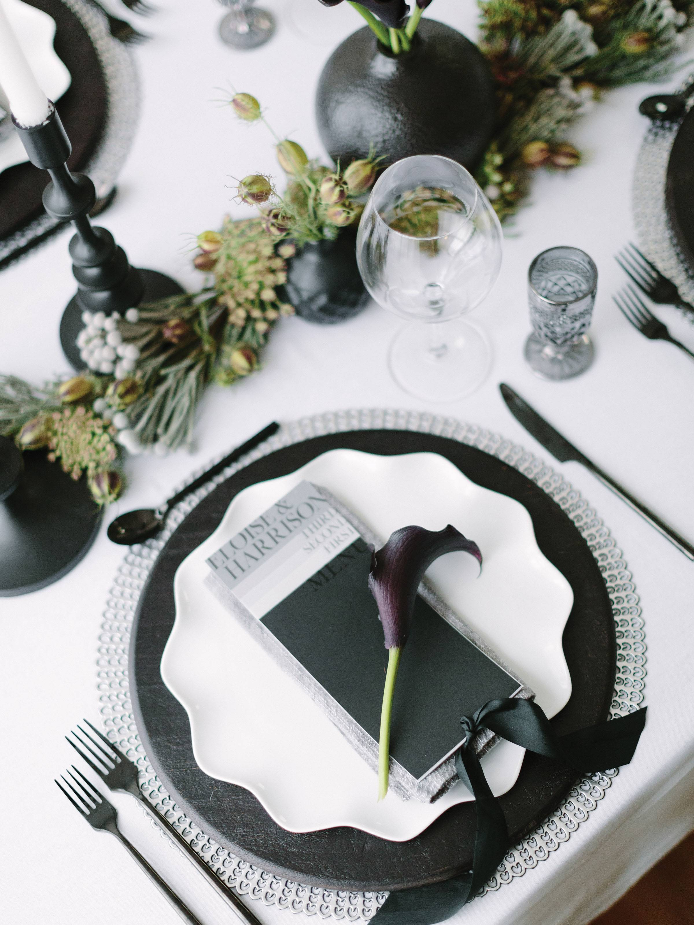 table setting with black and silver chargers, white scalloped plate, black and silver place card and