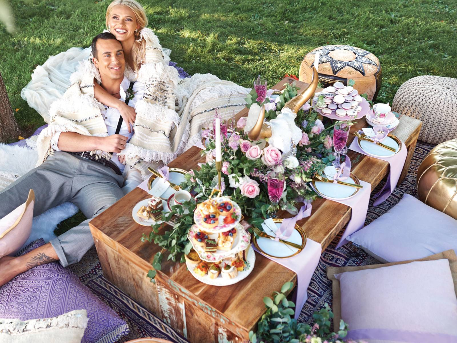 Bride and groom lounging by rustic wood table with pink and lavender florals, desserts and china
