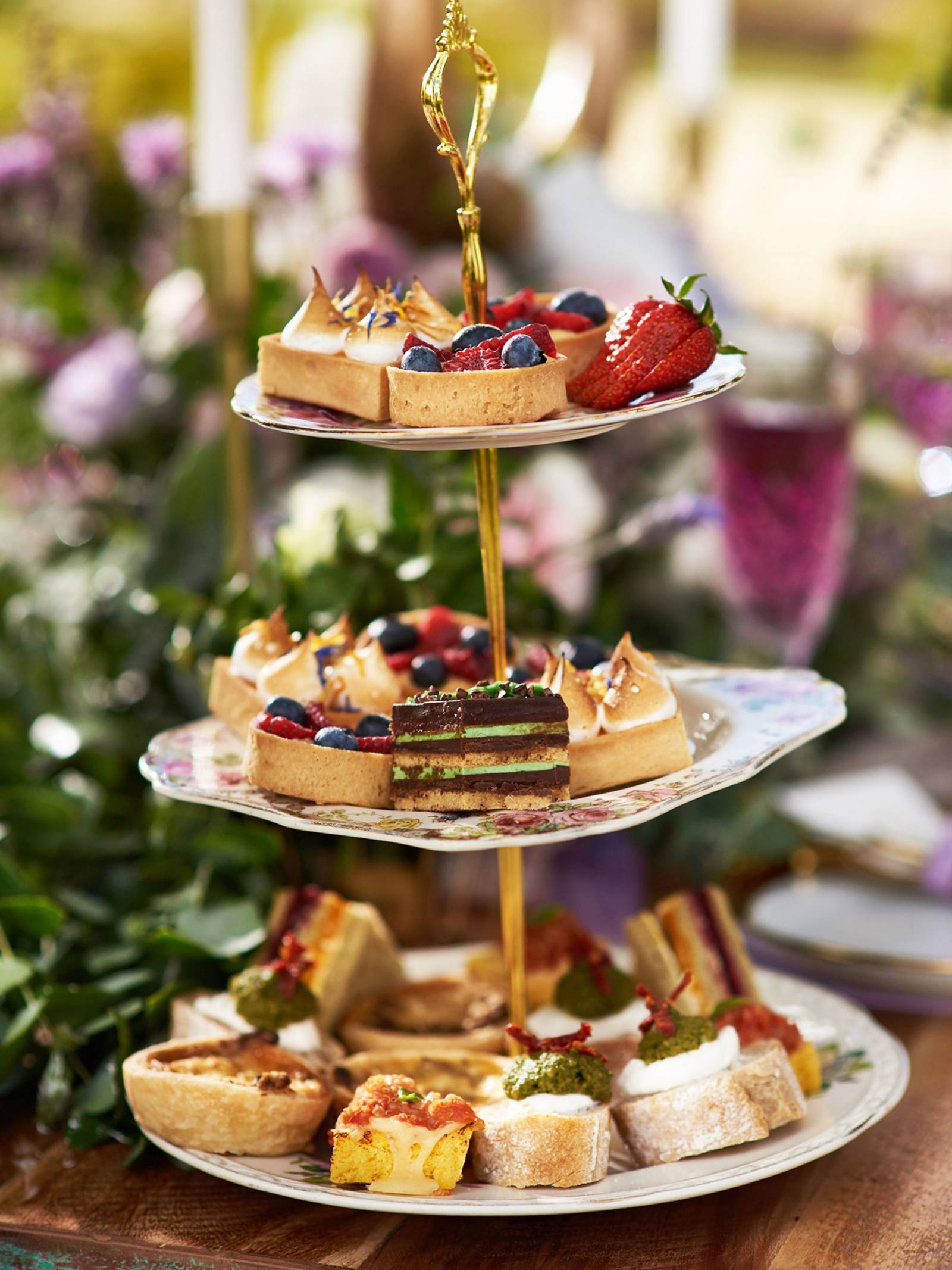 Three tiered dessert tower with fruit, tarts, meringue pastries