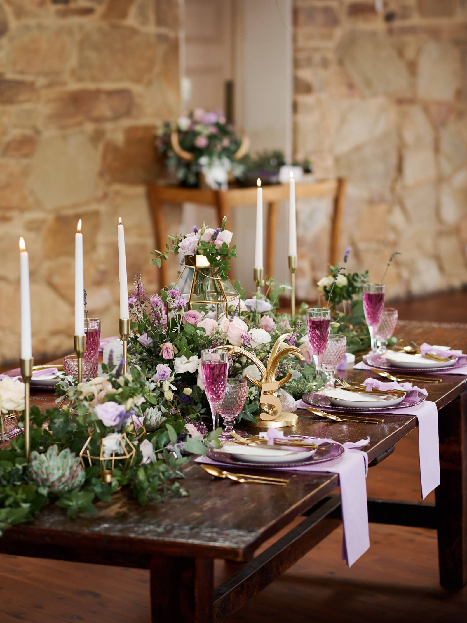 Wood table with pink and lavender florals and napkins, tapered candles, china and crystal