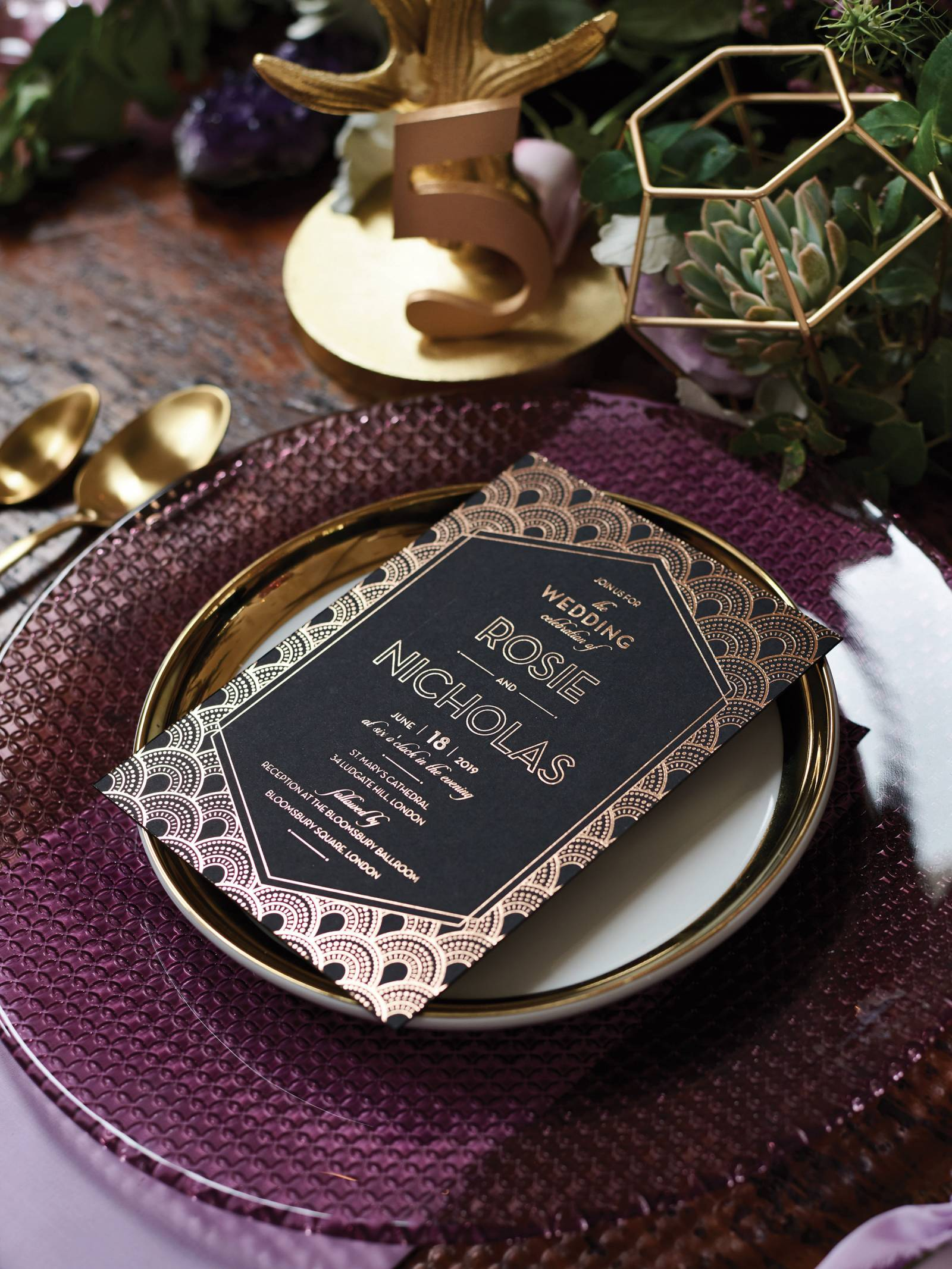 Gatsby styled wedding invitation in black and gold on a gold rimmed plate and purple charger