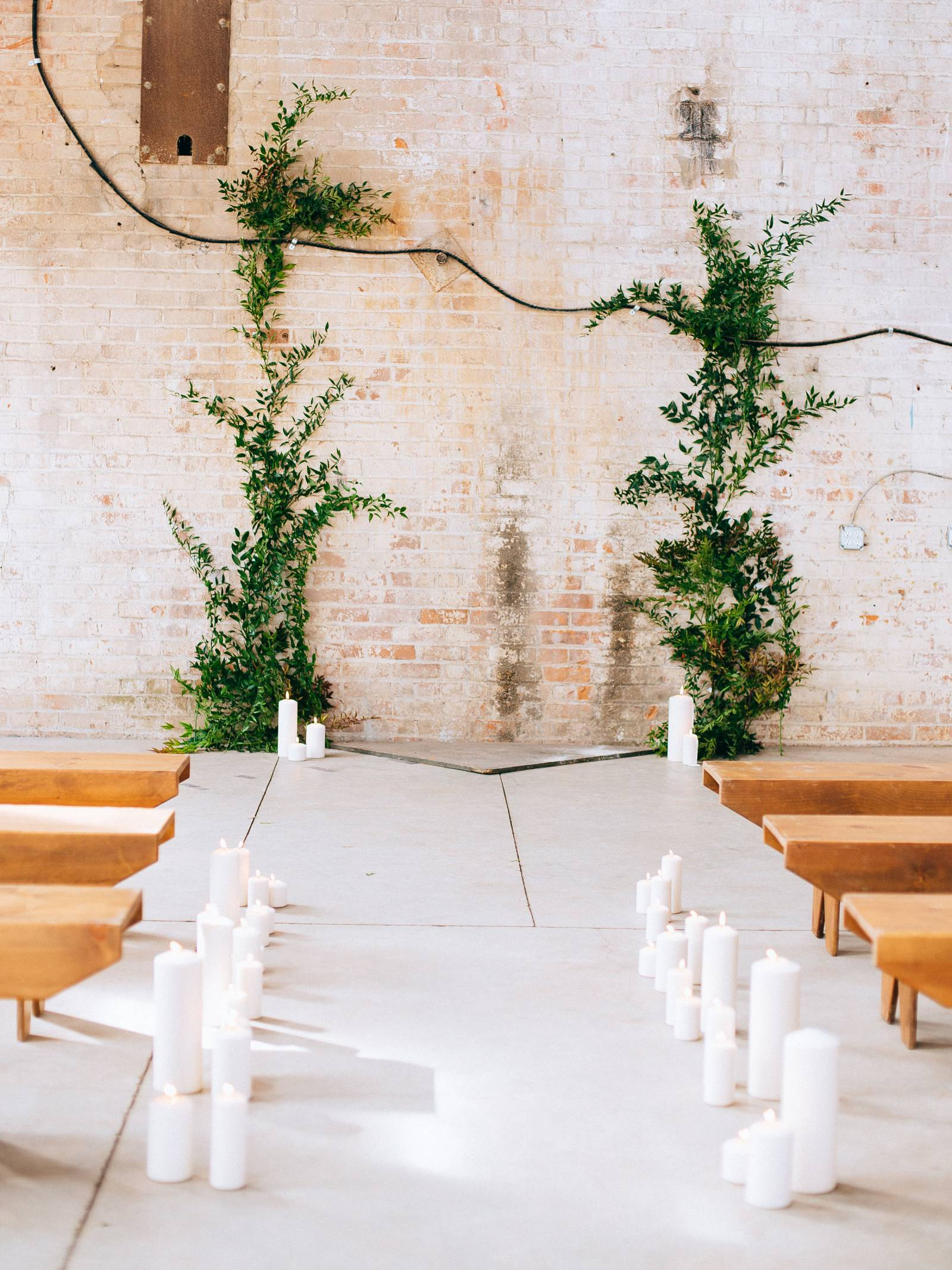 Ceremony aisle flanked with white pillar candles and wood benches and two columns of greenery