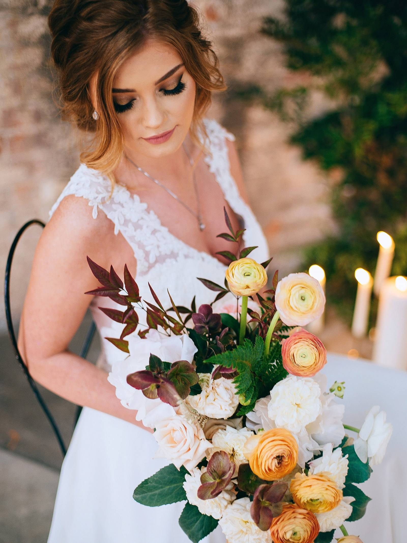 Bride holding bouquet of peach, pink, coral and blush peonies and ranunculus