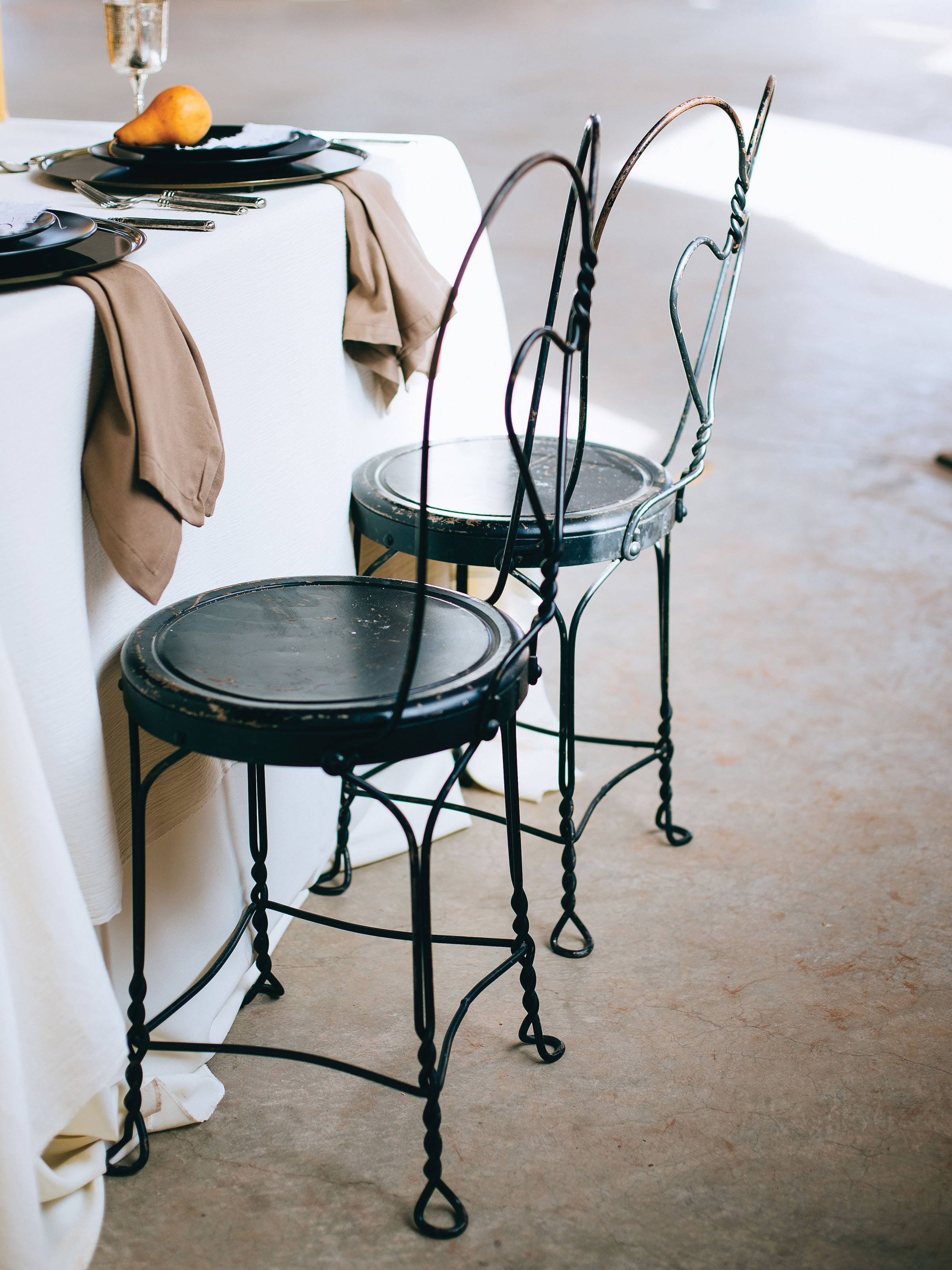 Black bistro chairs by a table draped in white linen with beige napkins and black plates