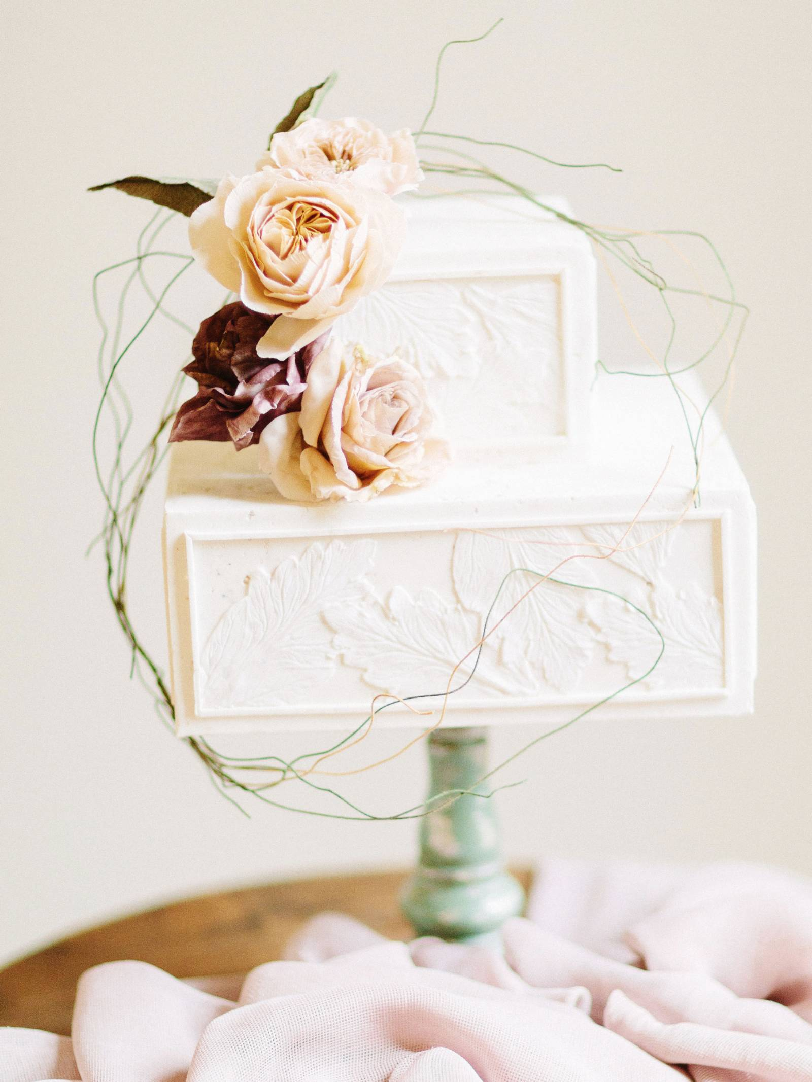Two-tiered, square, ivory cake with blush flower accents