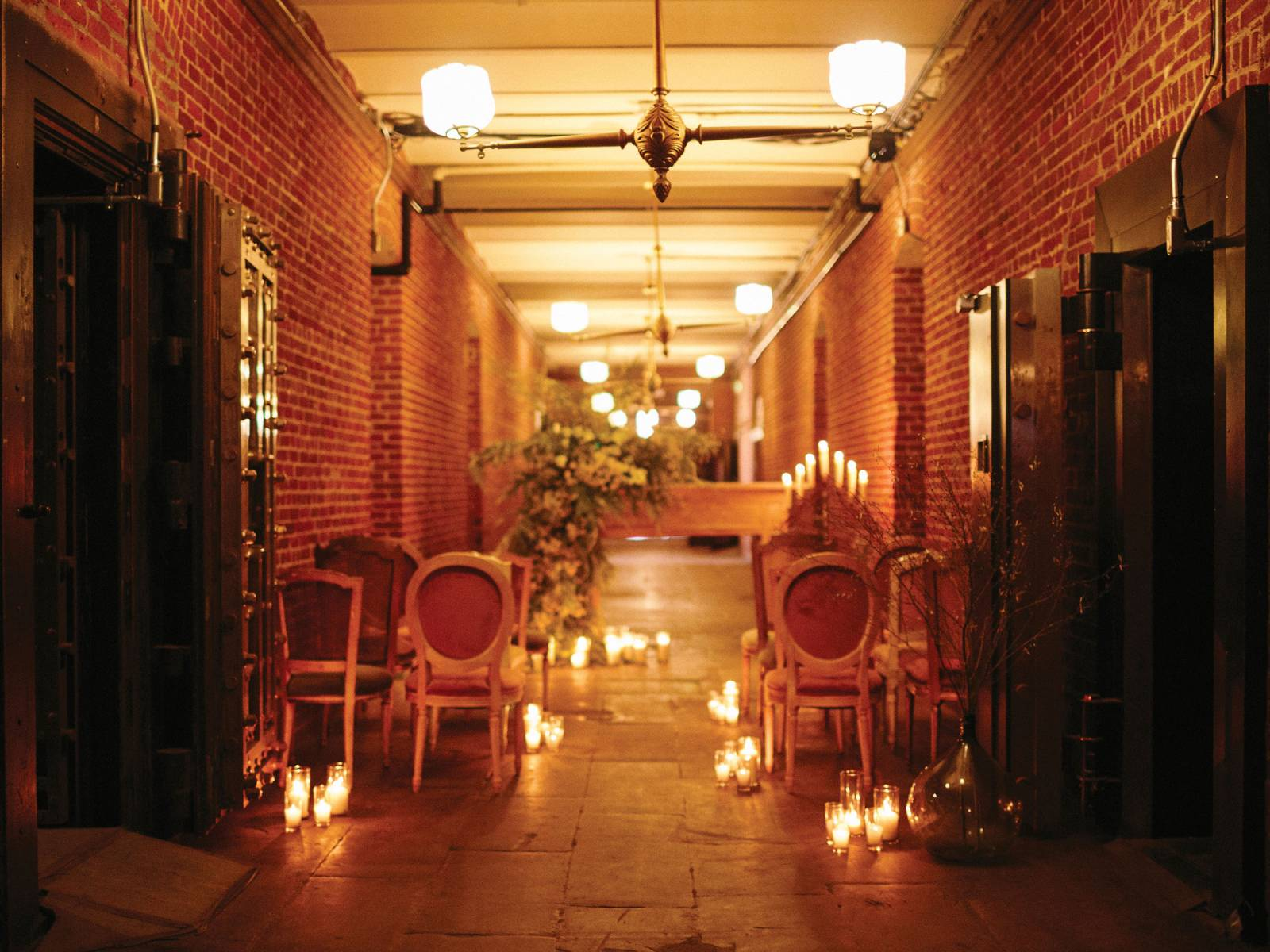 Brick corridor set-up for a ceremony with floral draped altar, seating and candles