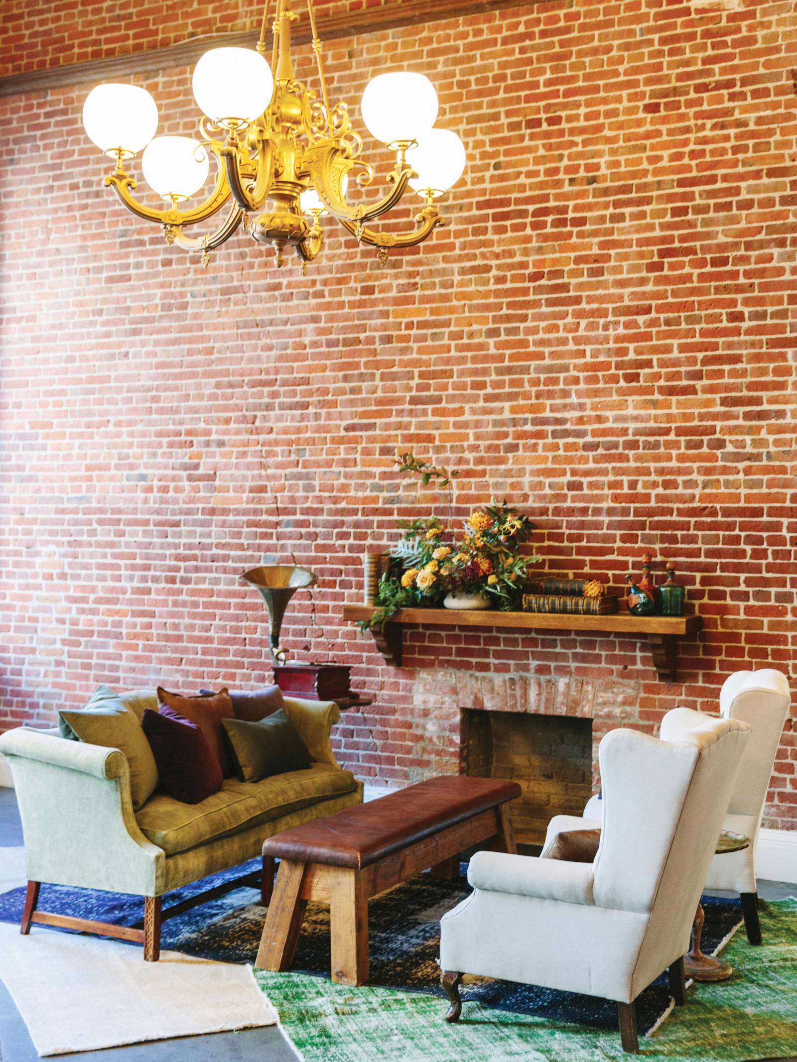 Vintage sage green couch and cream velvet chairs by brick wall