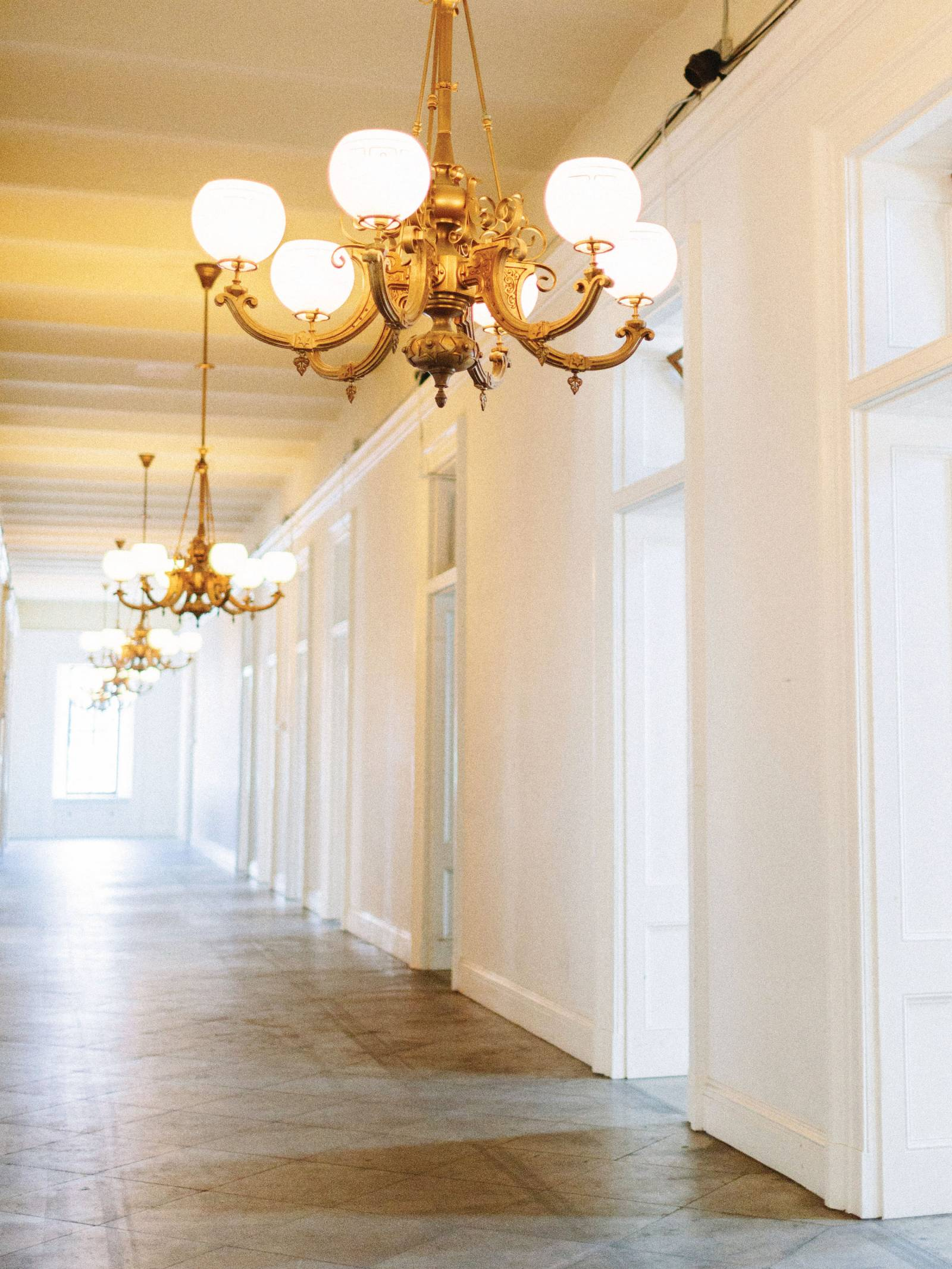 White walled hallway with vintage gold chandeliers at The San Francisco Mint