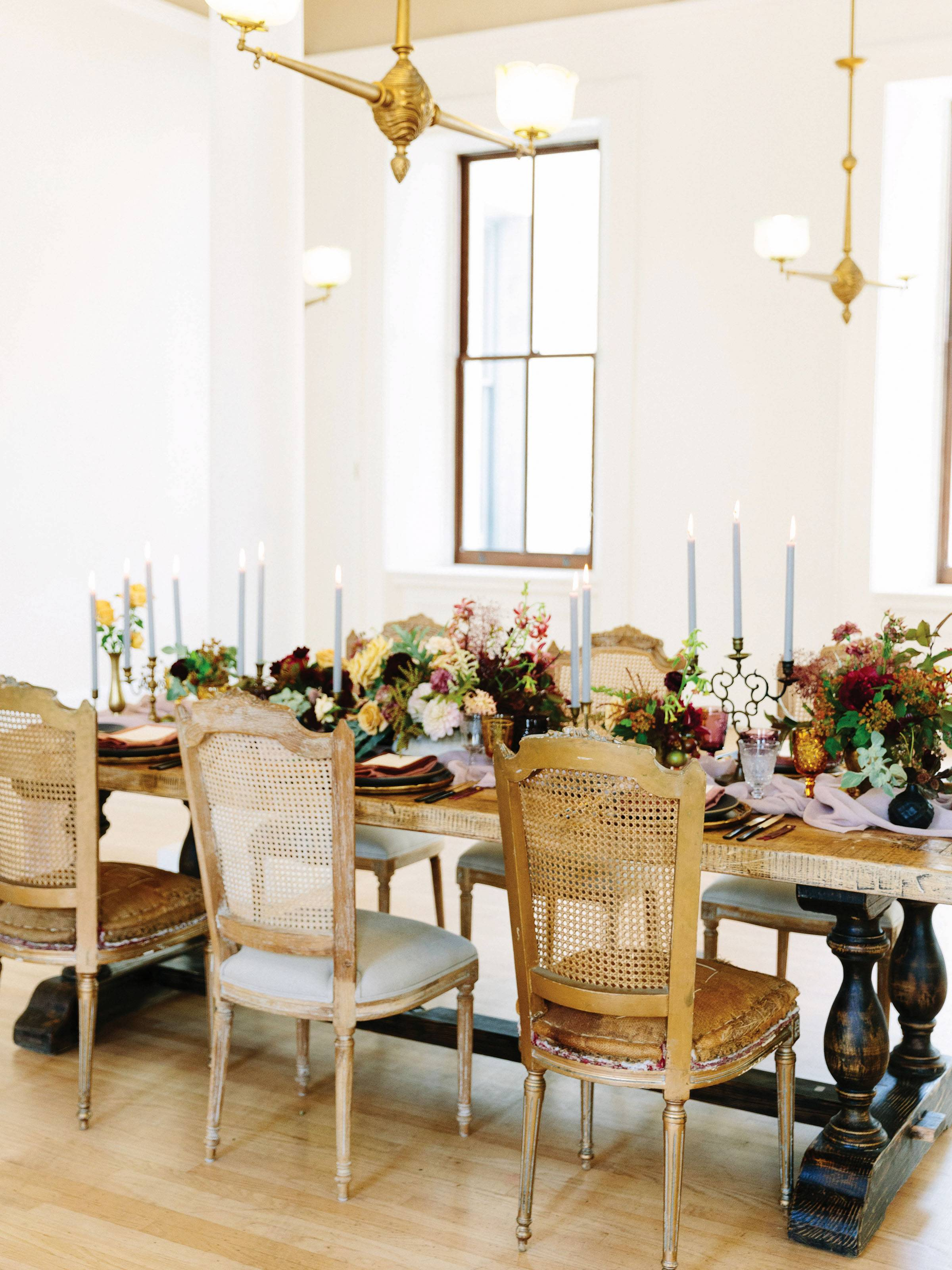 rustic table with fall flowers, black plates and vases, vintage chairs and lavender tapered candles