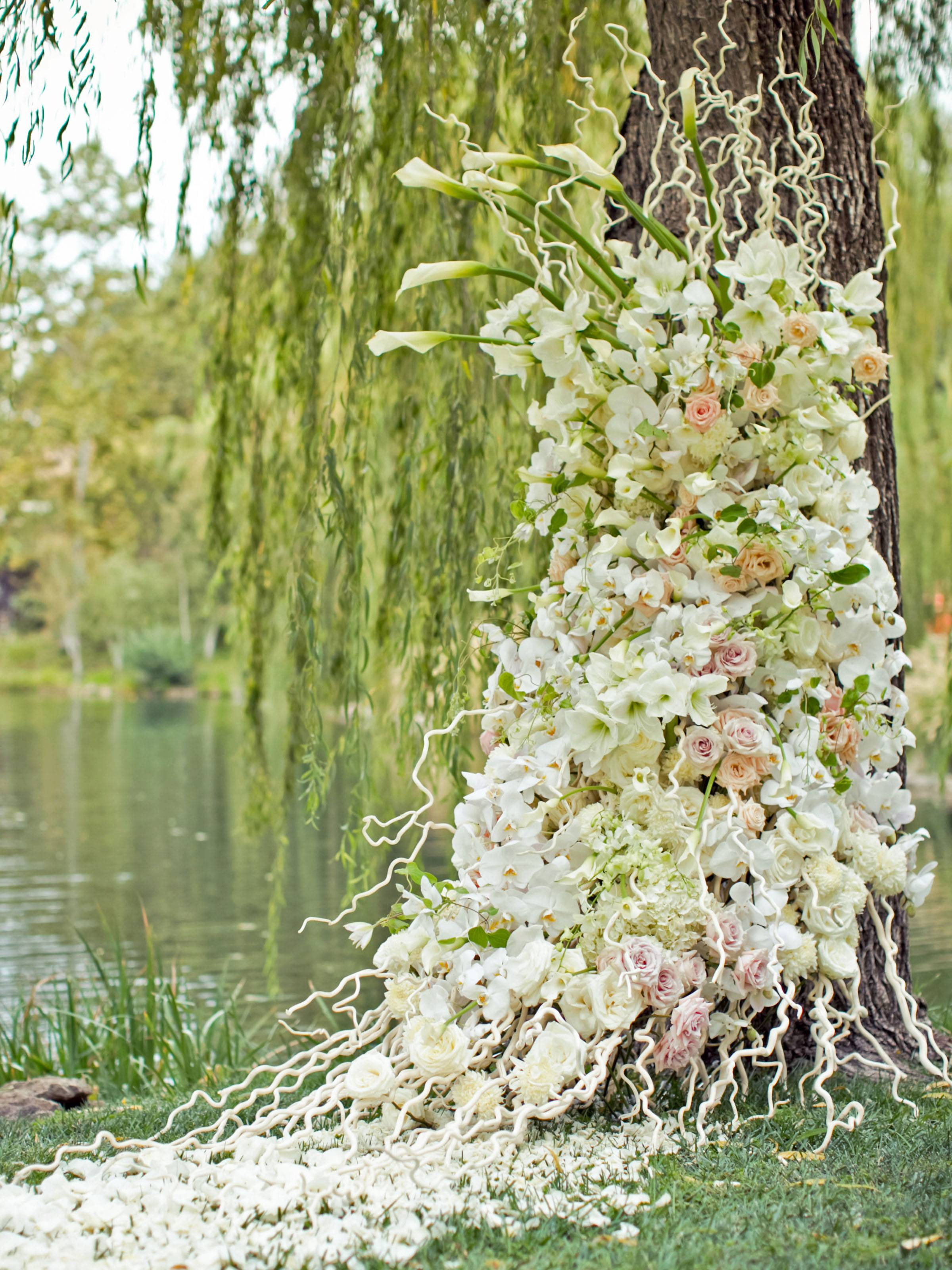 Lush white, blush and peach florals winding up a tree trunk