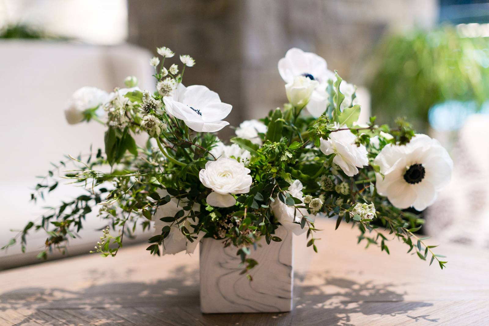 White blooms and greenery in square white container