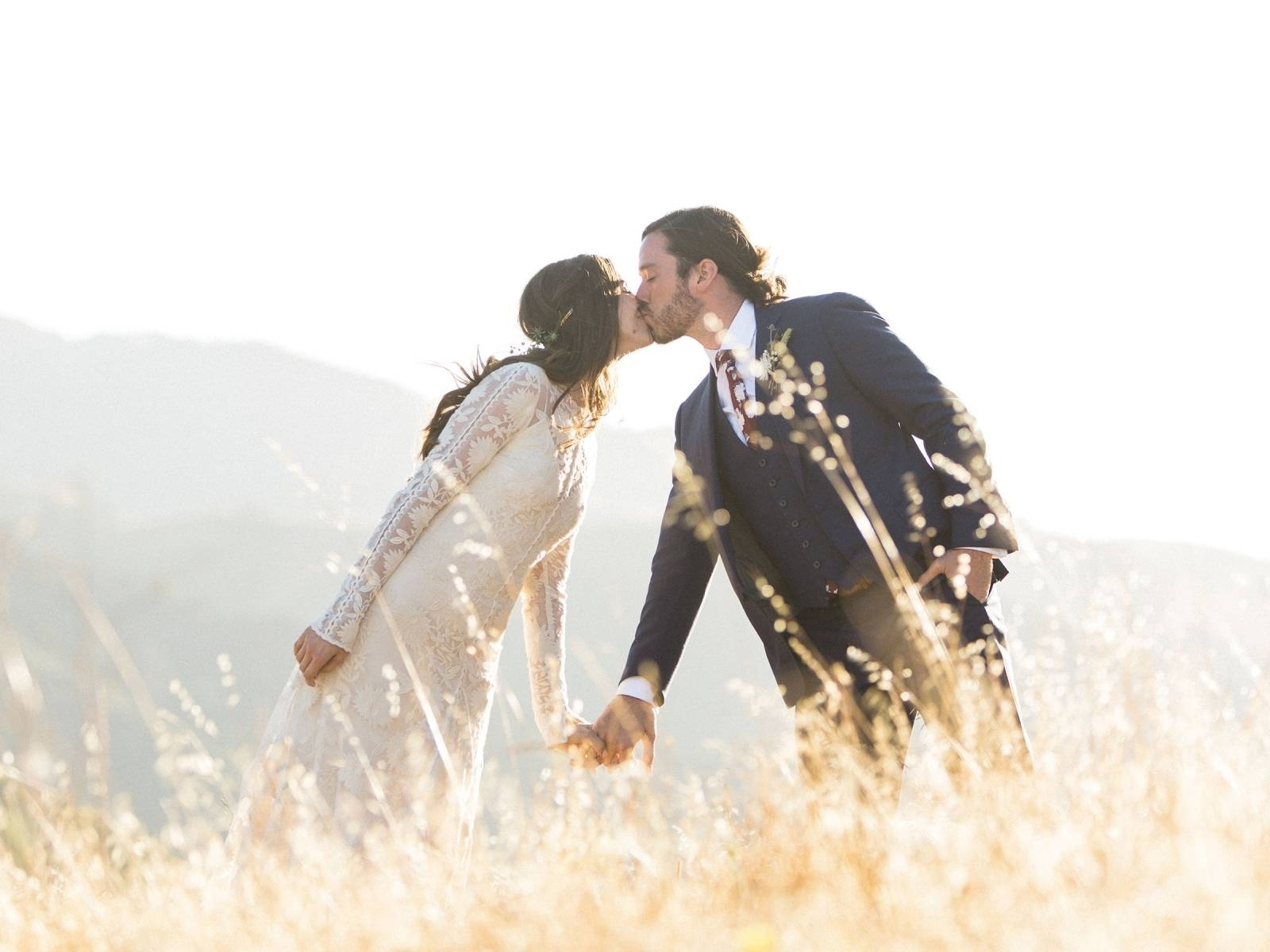 Bohemian bride and grooms kissing