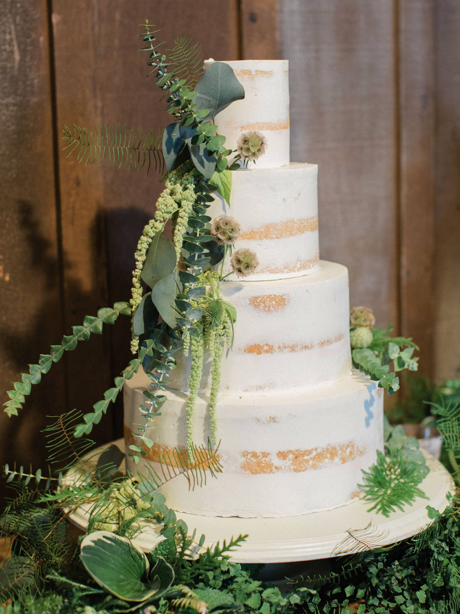 naked white wedding cake with greenery