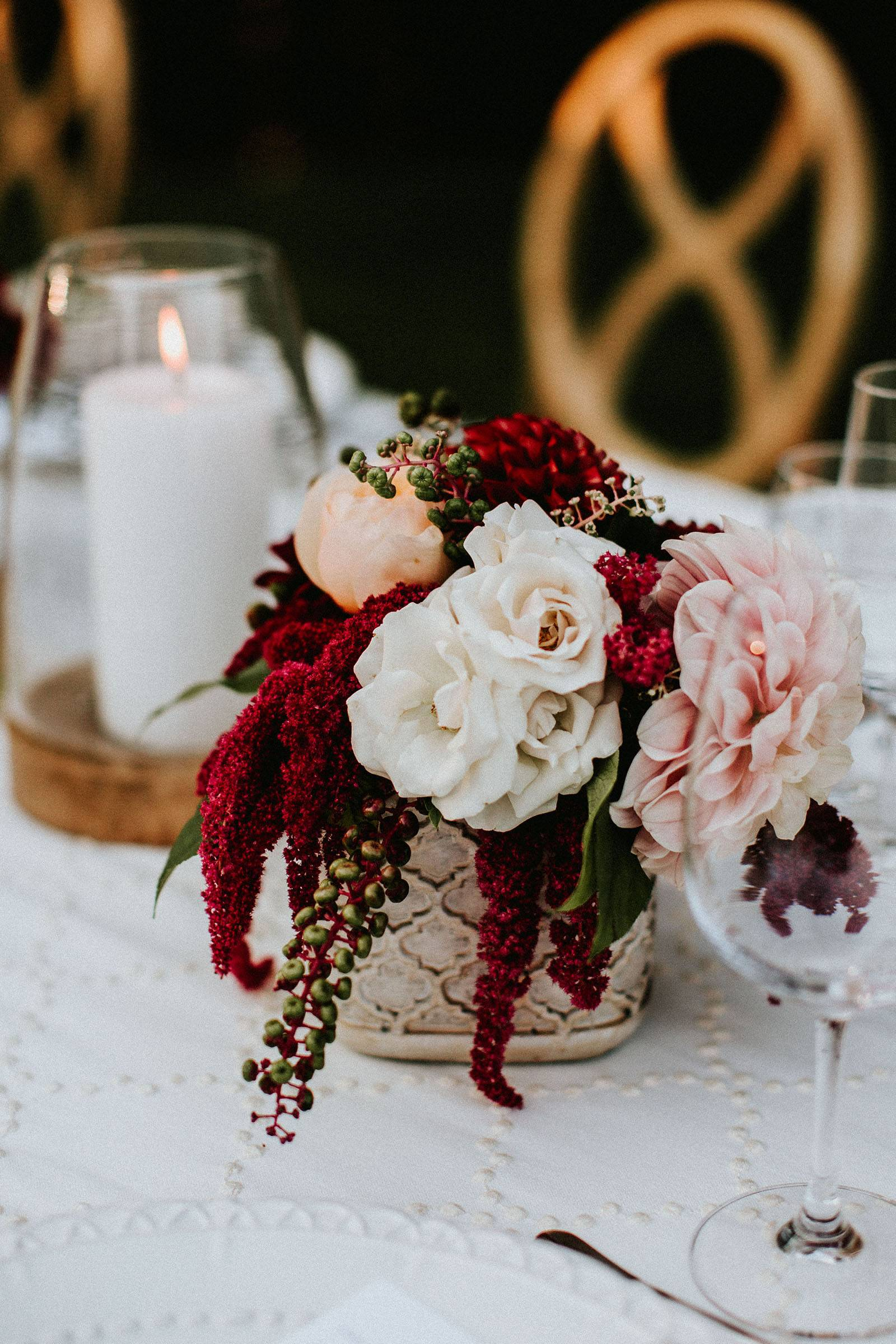 burgundy and blush floral centerpiece and candle