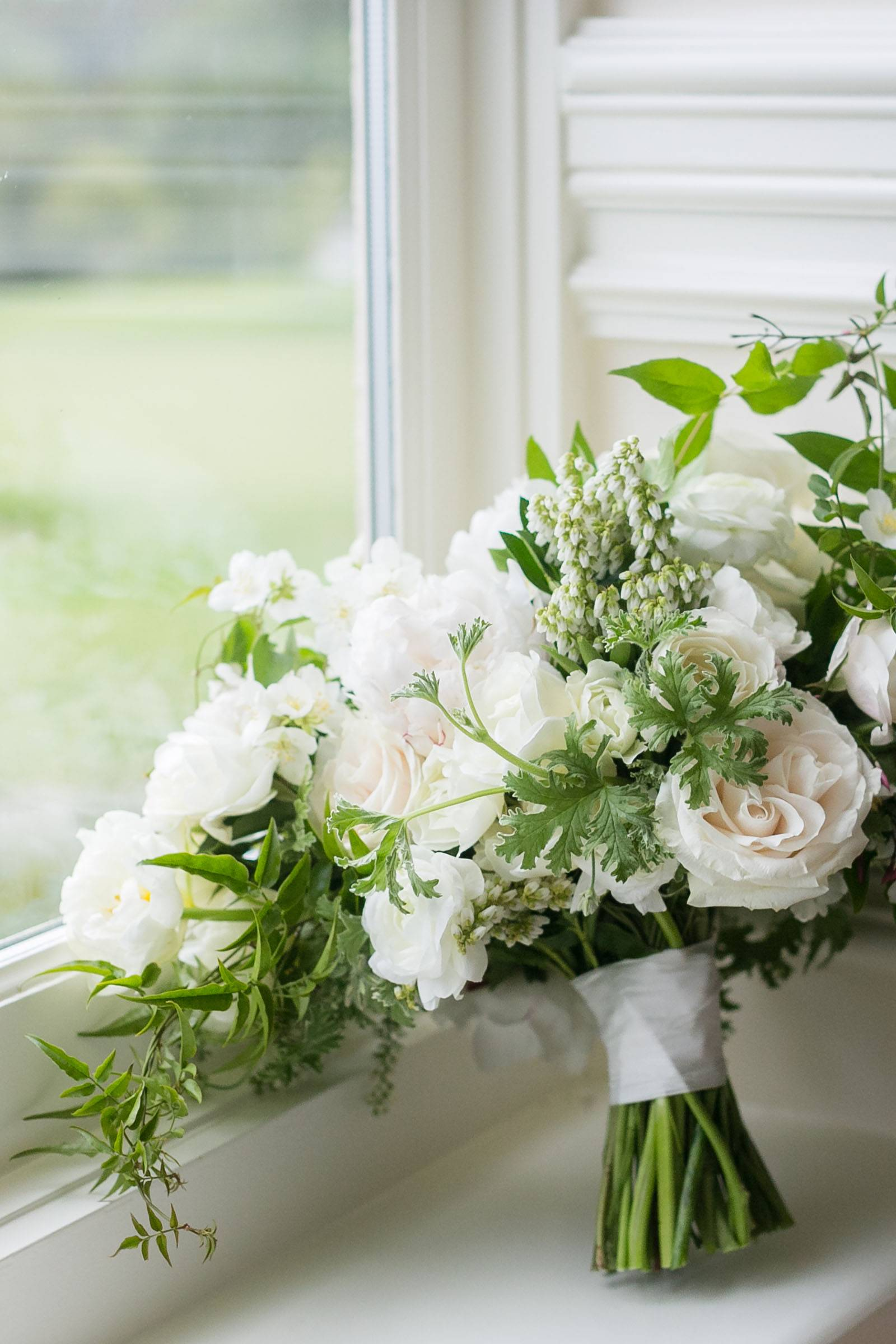 white crescent wedding bouquet with greenery