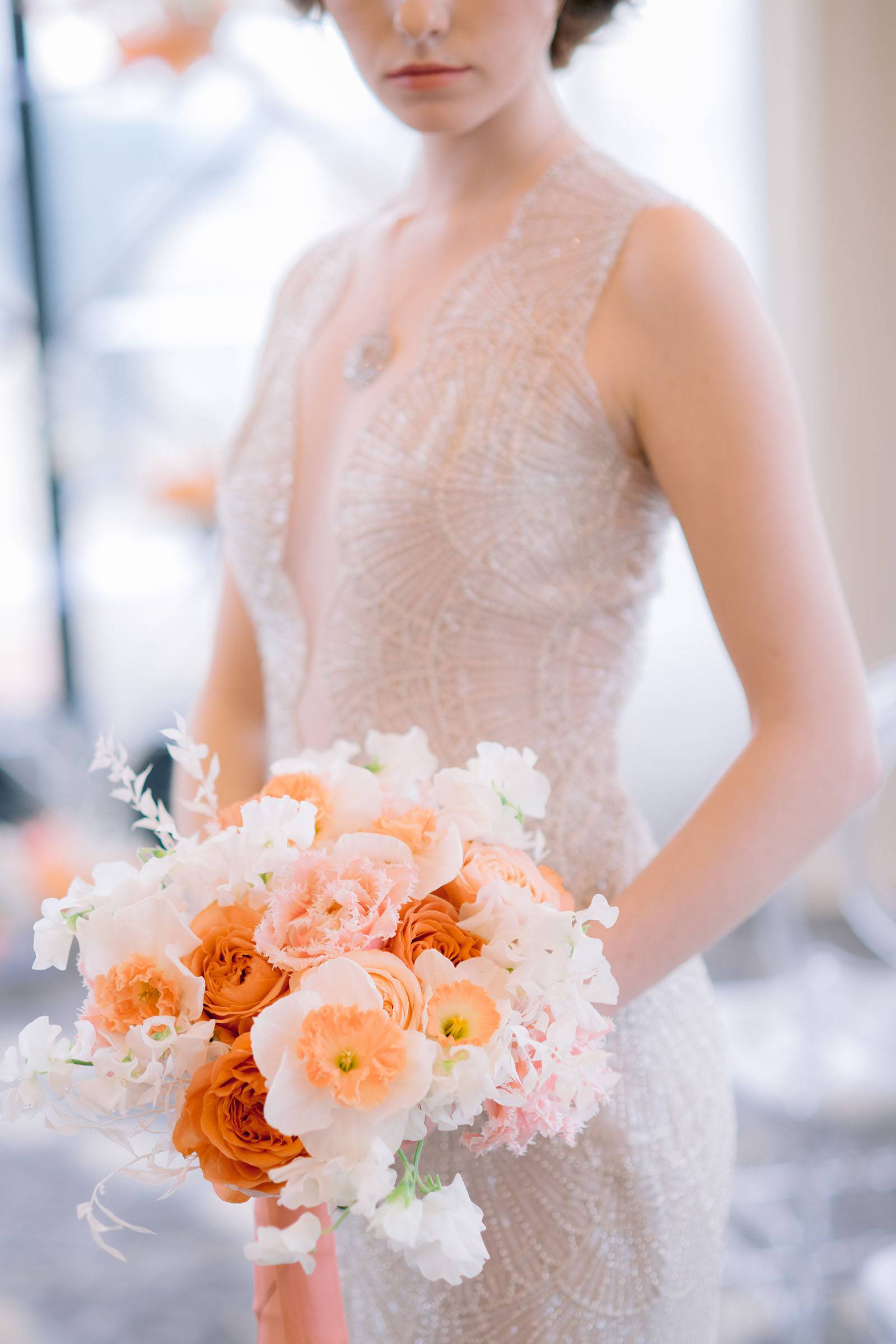 Beaded bridal gown and bouquet in coral, peach and white