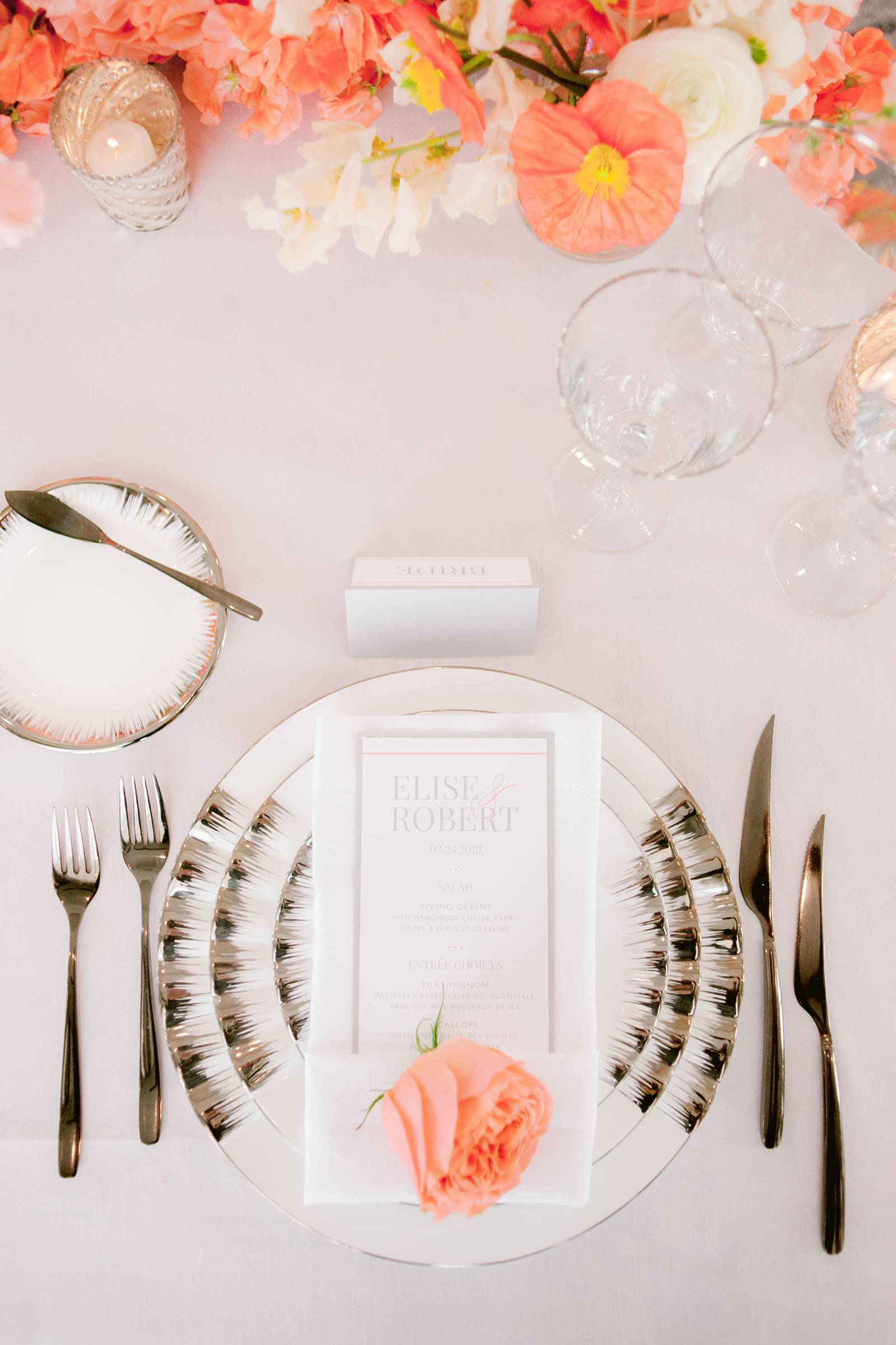 White and silver place setting and living coral flowers