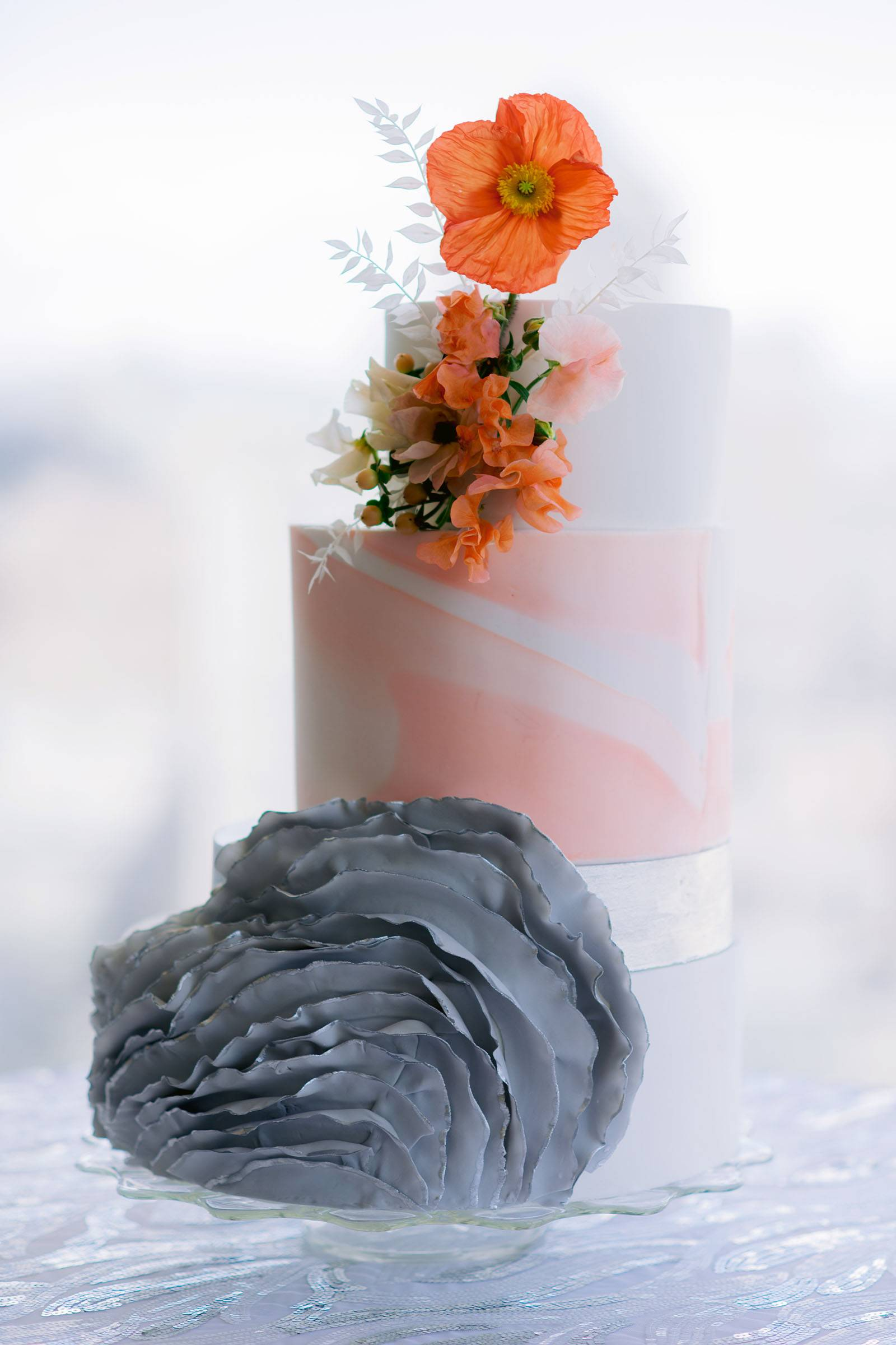 White and coral wedding cake with gray ruffle