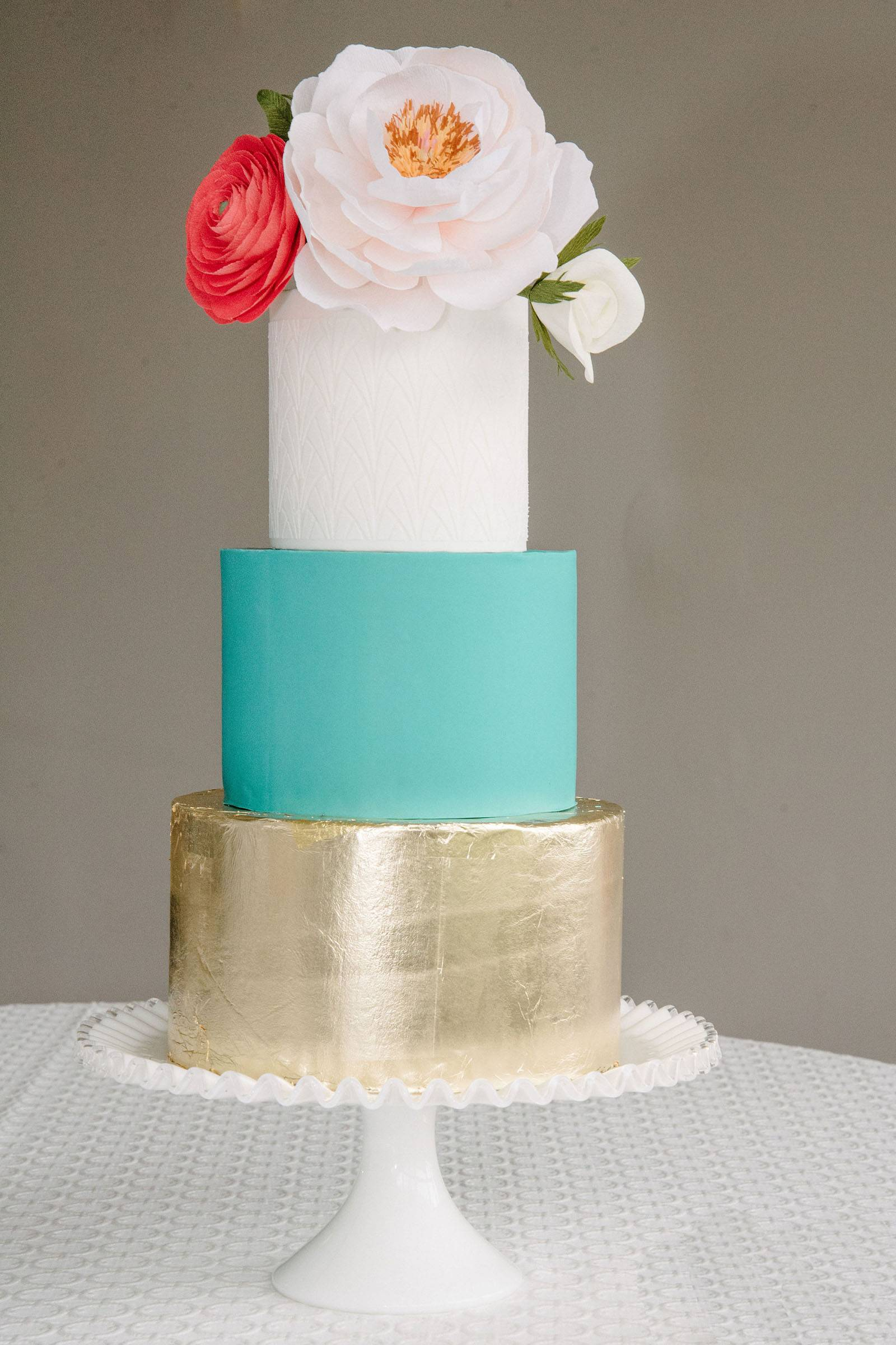 Three tiered cake in white, aqua and gold foil