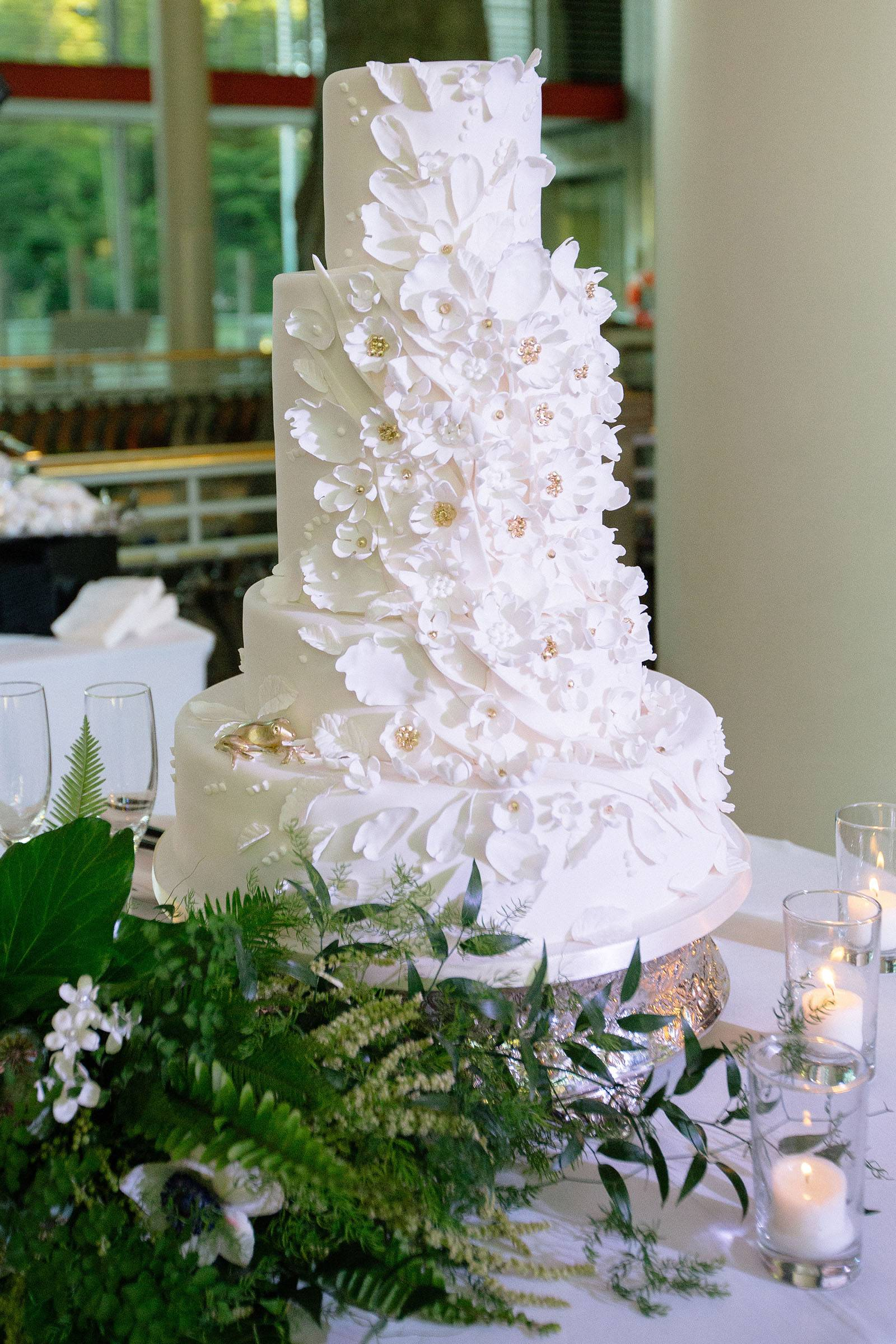 Three tiered wedding cake with white petal decorations and gold accents.
