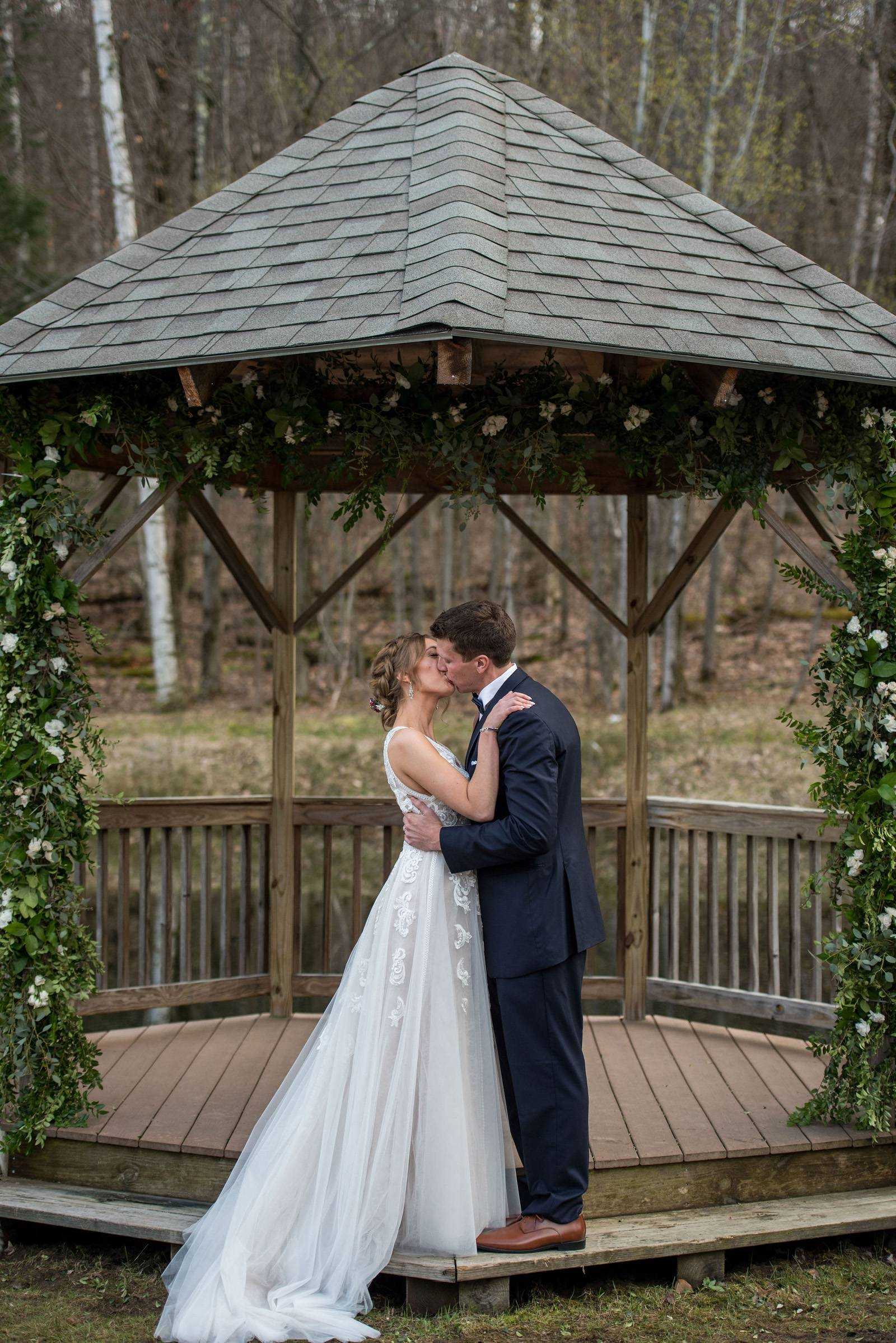 Bride and groom exchange vows under gazebo at Sleepy Hollow during spring Vermont wedding