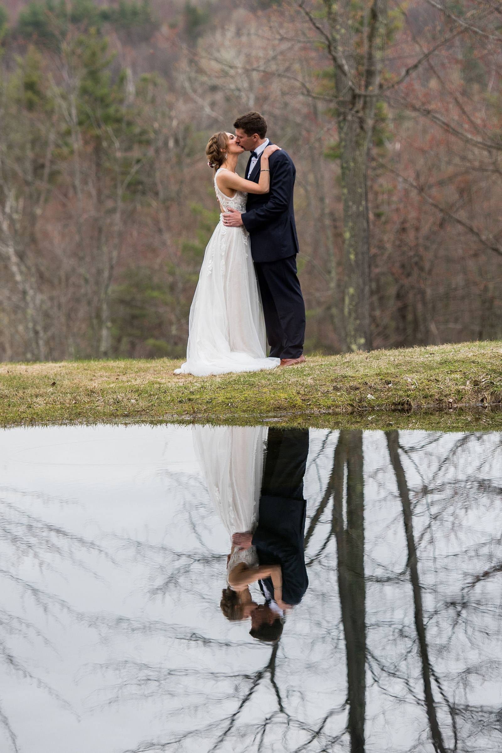 Portrait of bride and groom kissing, reflected in pond at Sleepy Hollow Inn in Vermont on spring wed
