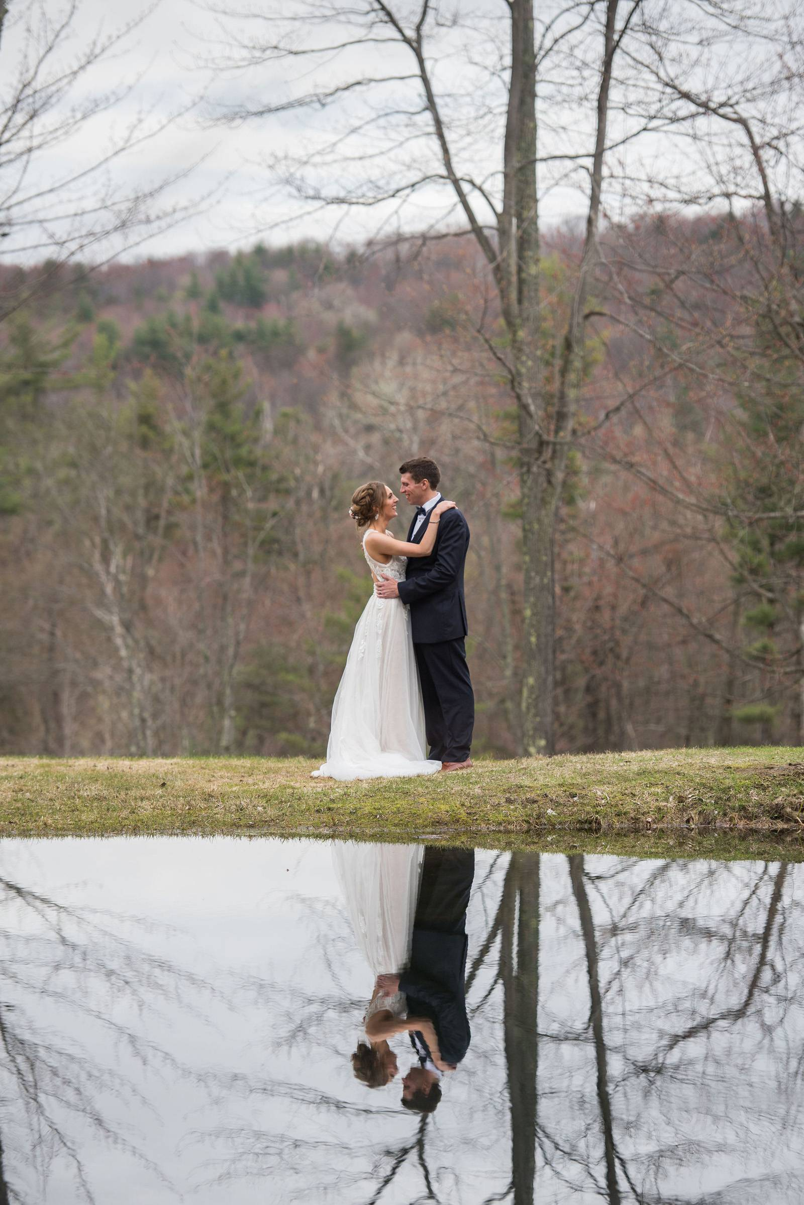 Portrait of bride and groom reflected in pond at Sleepy Hollow Inn in Vermont on spring wedding day