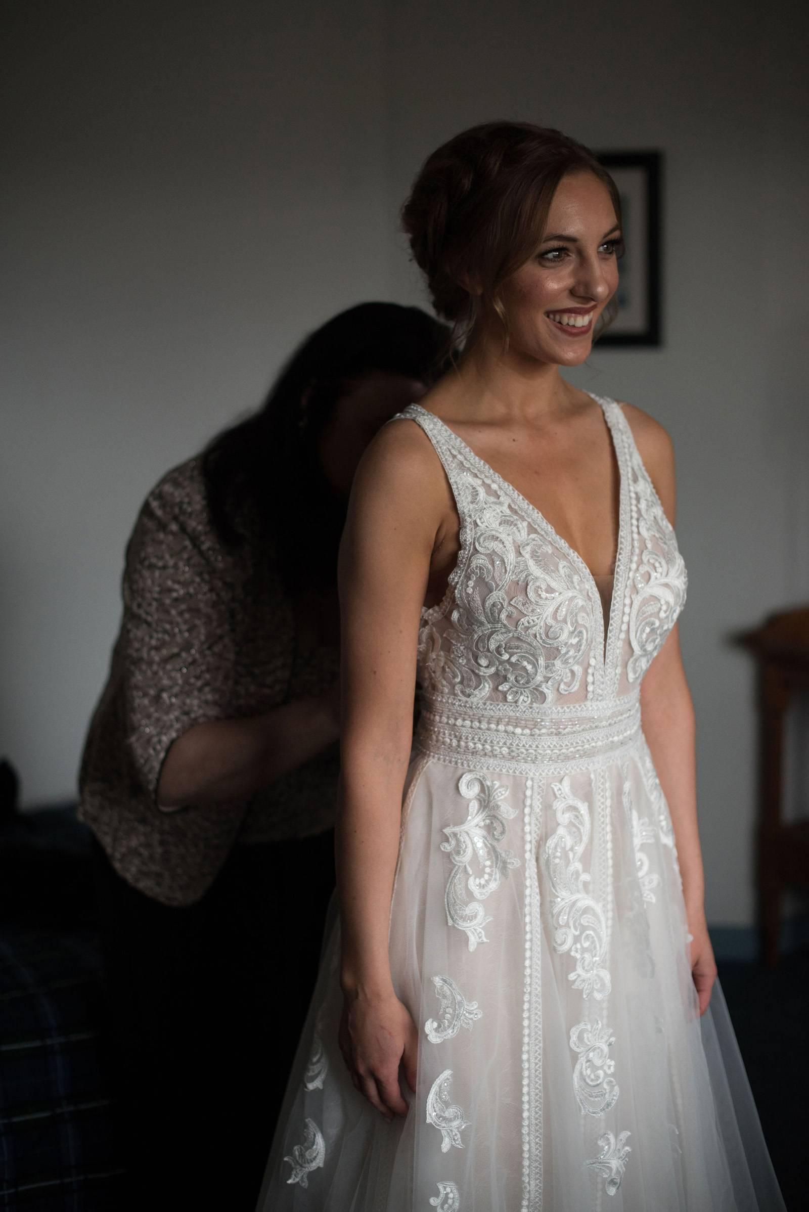 bride putting on her wedding dress with her mom's help