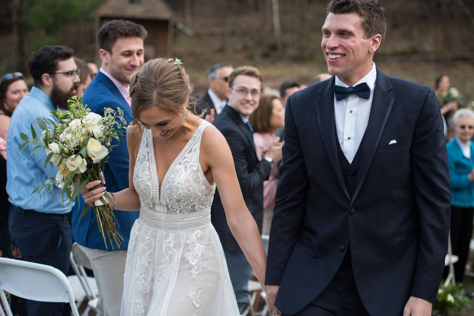 Bride and groom walking down the aisle at Sleepy Hollow during spring Vermont wedding