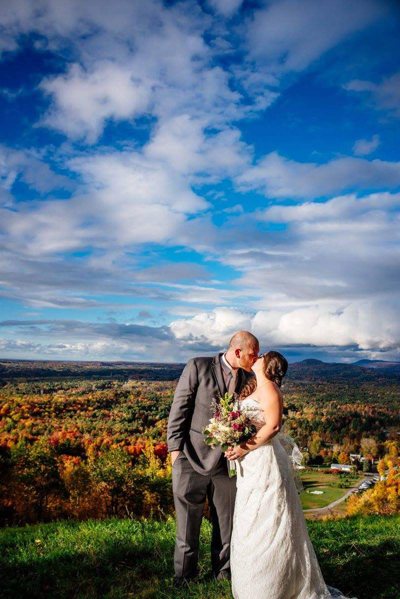 Couple kissing at fall wedding at Sharp Farm in Milton Vermont during fall wedding overlooking the m