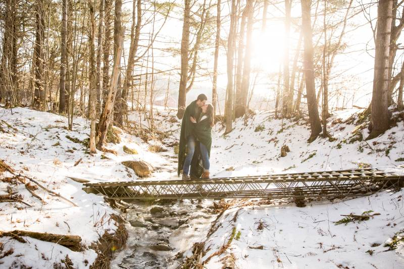 Couple kissing under a blanket during winter engagement photo shoot